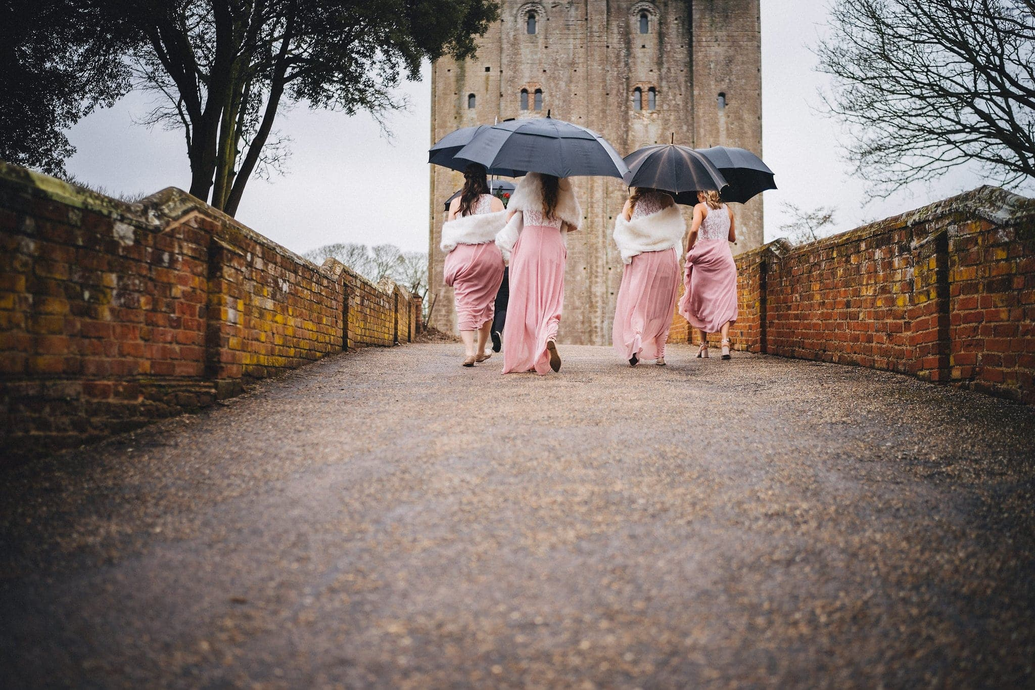 Bridesmaids walk into Hedingham Castle holding umbrellas
