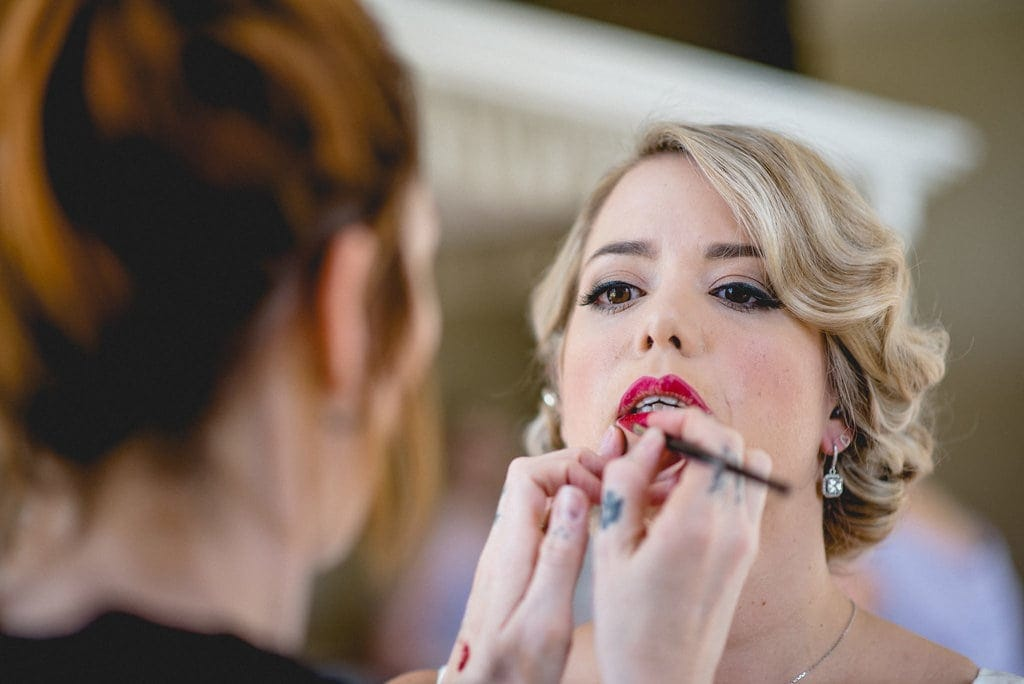 Bride has red lipstick applied