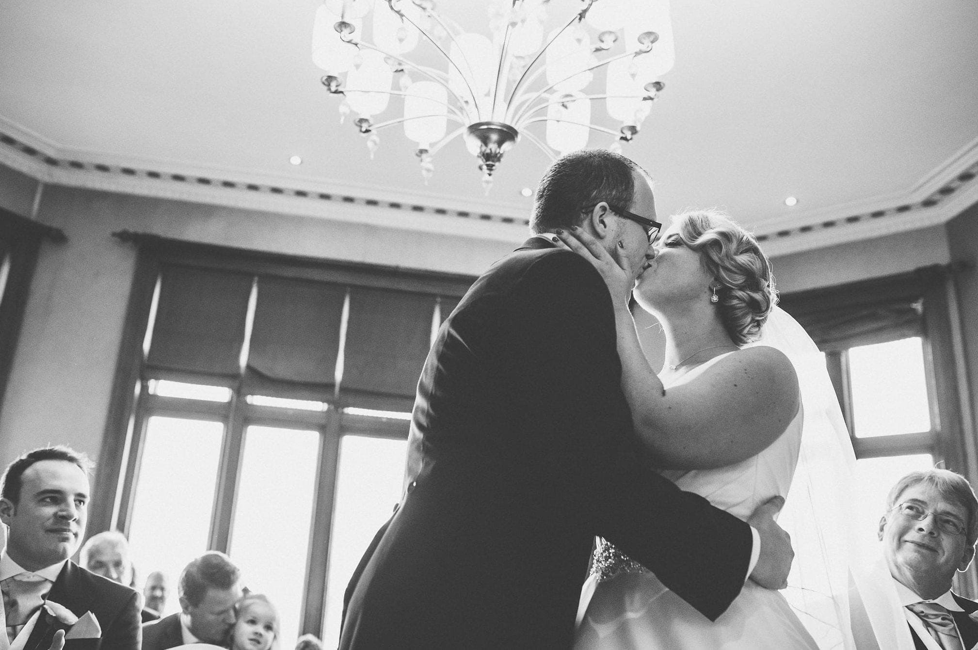 Black and white shot of bride and groom kissing during wedding ceremony