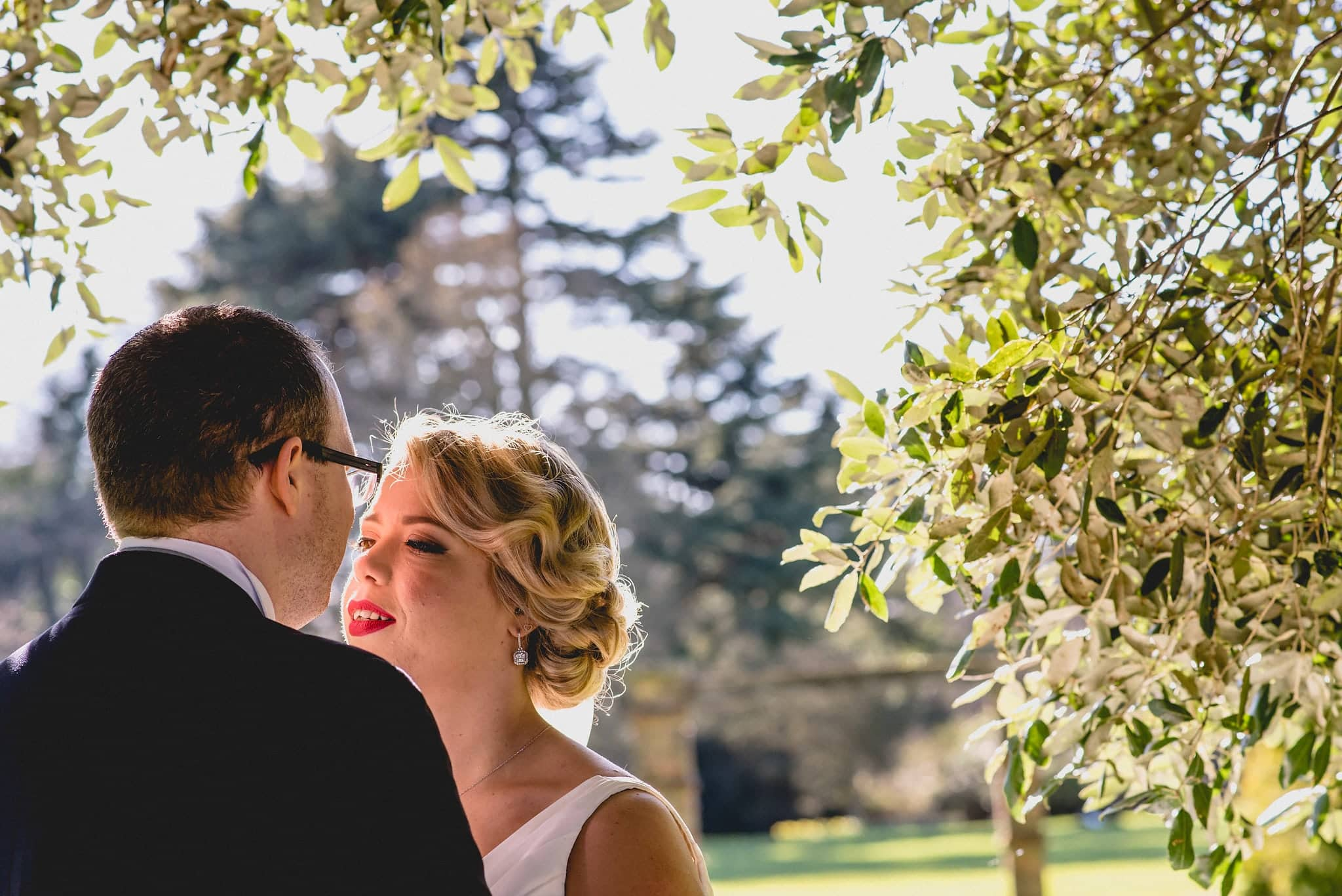 Bride and groom kiss under trees at Shendish Manor
