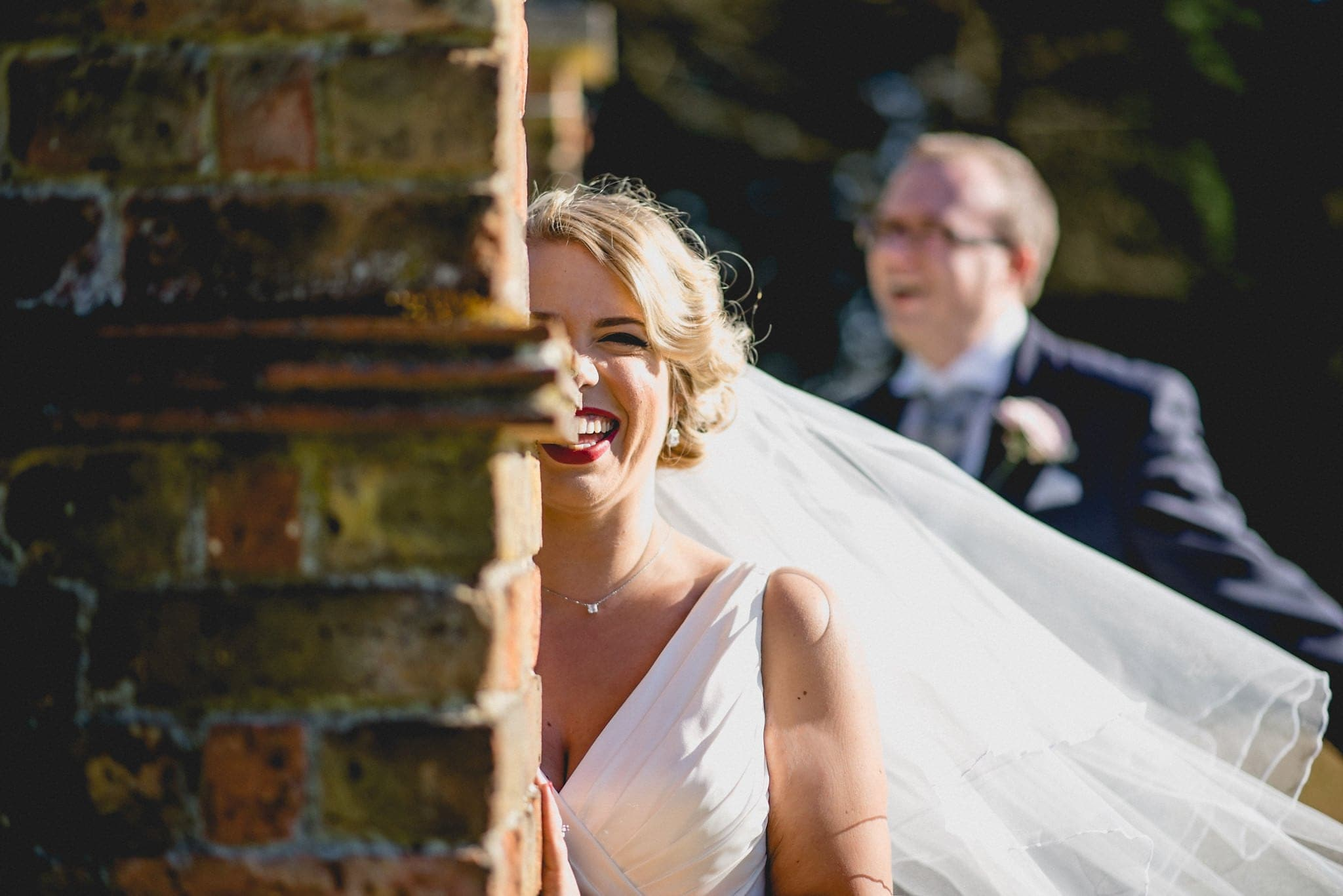 Bride and groom peeping out behind stonework at Shendish Manor