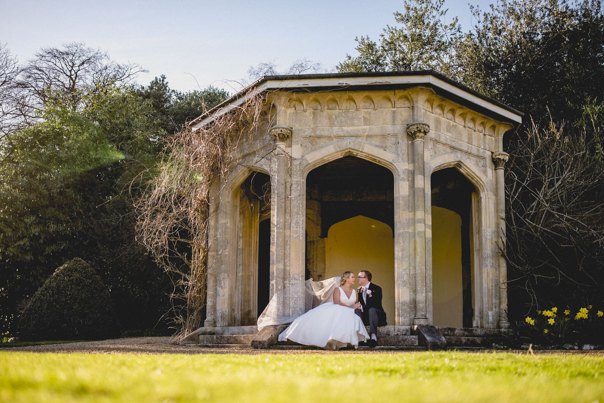Bride and groom sit together in stone pagoda in grounds of Shendish Manor