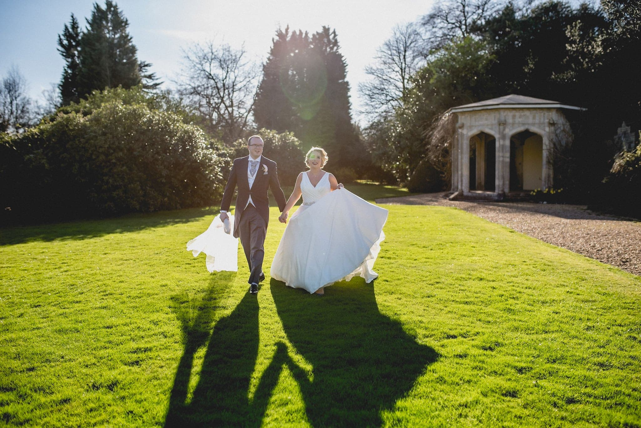 Bride and groom hold hands and cross the lawn at Shendish Manor