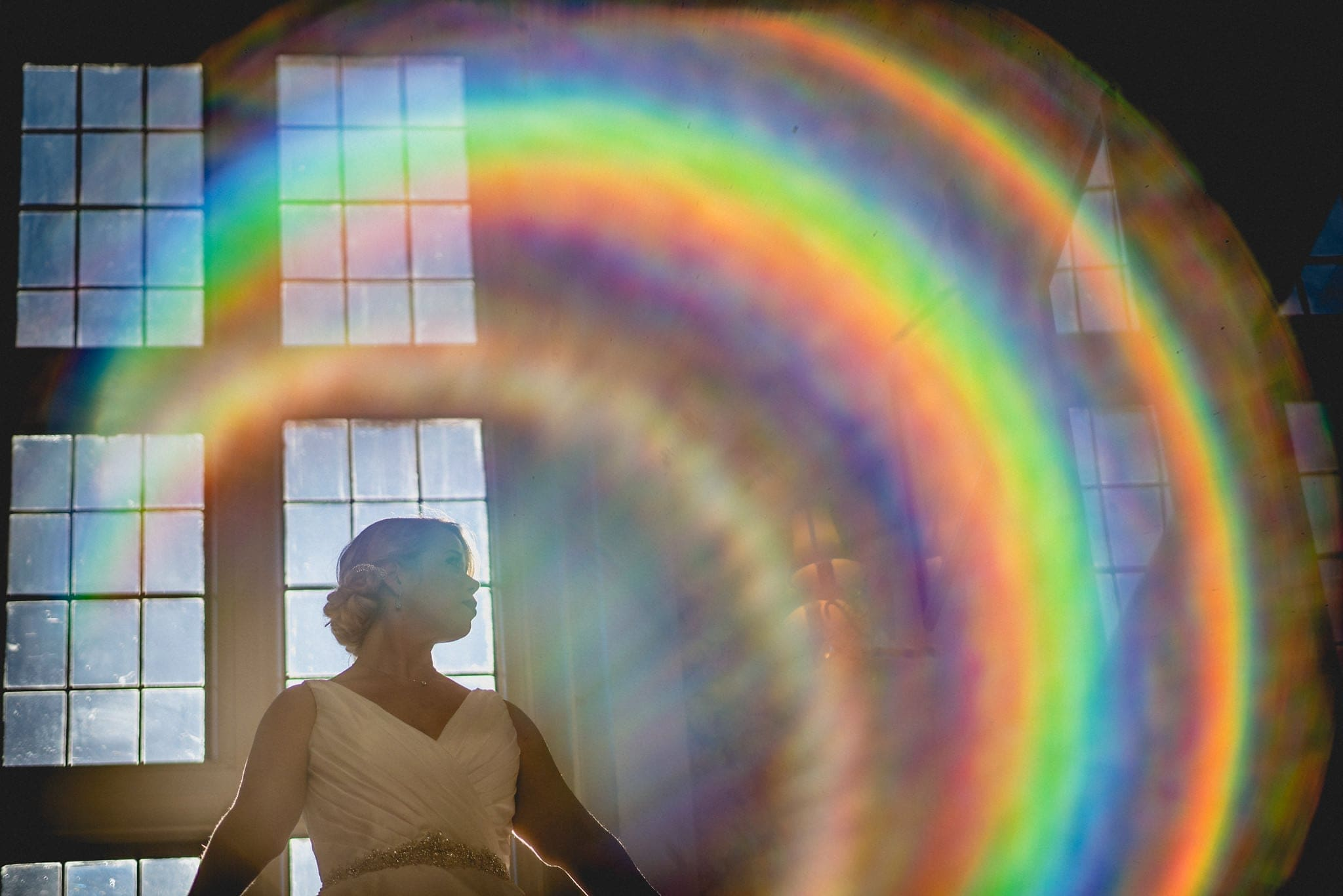 Bride poses in front of leaded window with rainbow lens flare