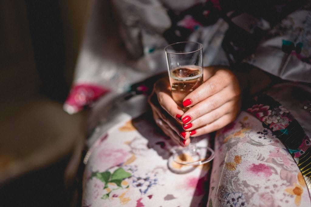 Bride with red nails holds glass of champagne as she gets ready for her Shendish Manor wedding