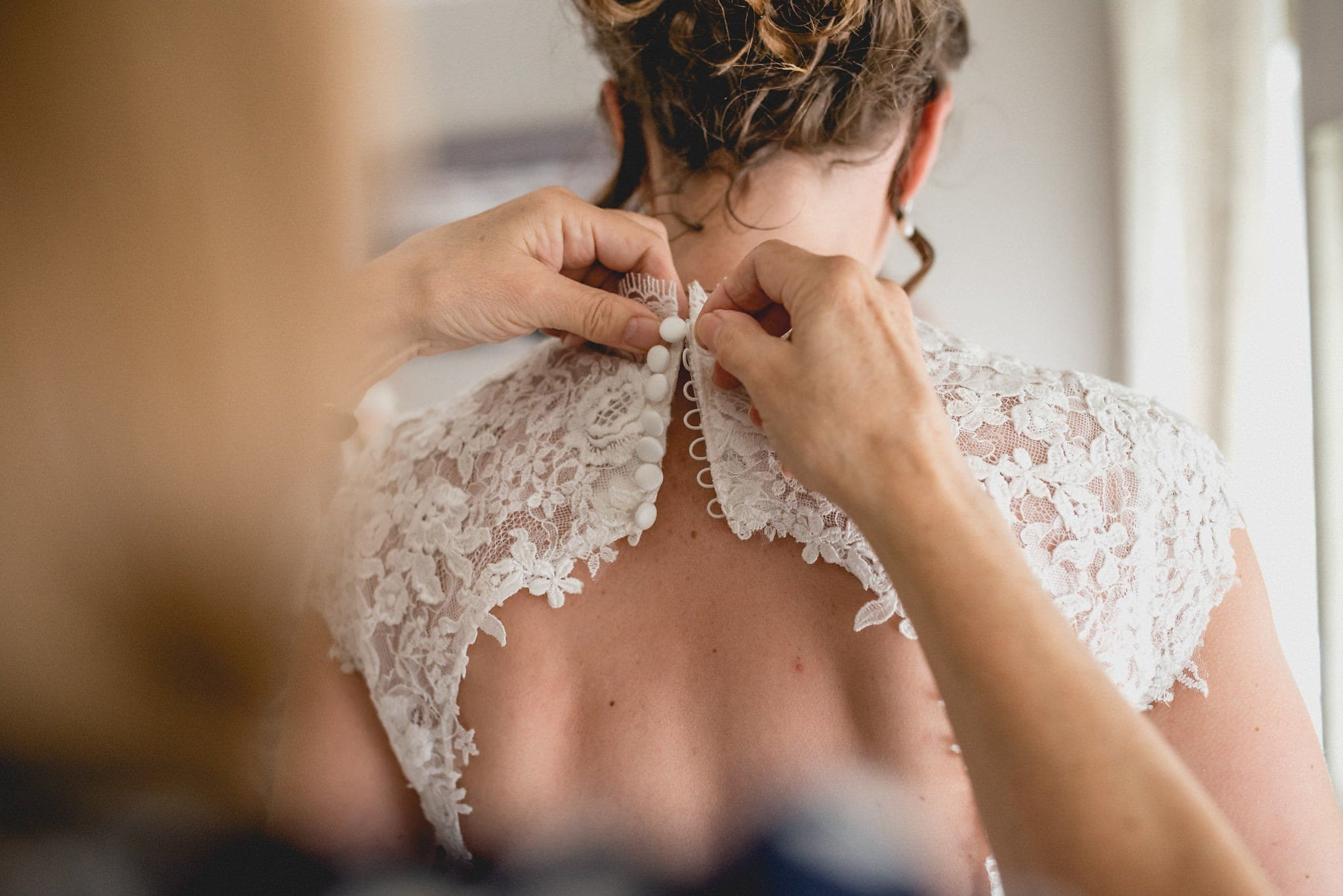 Bridesmaid fastens buttons on bride's dress