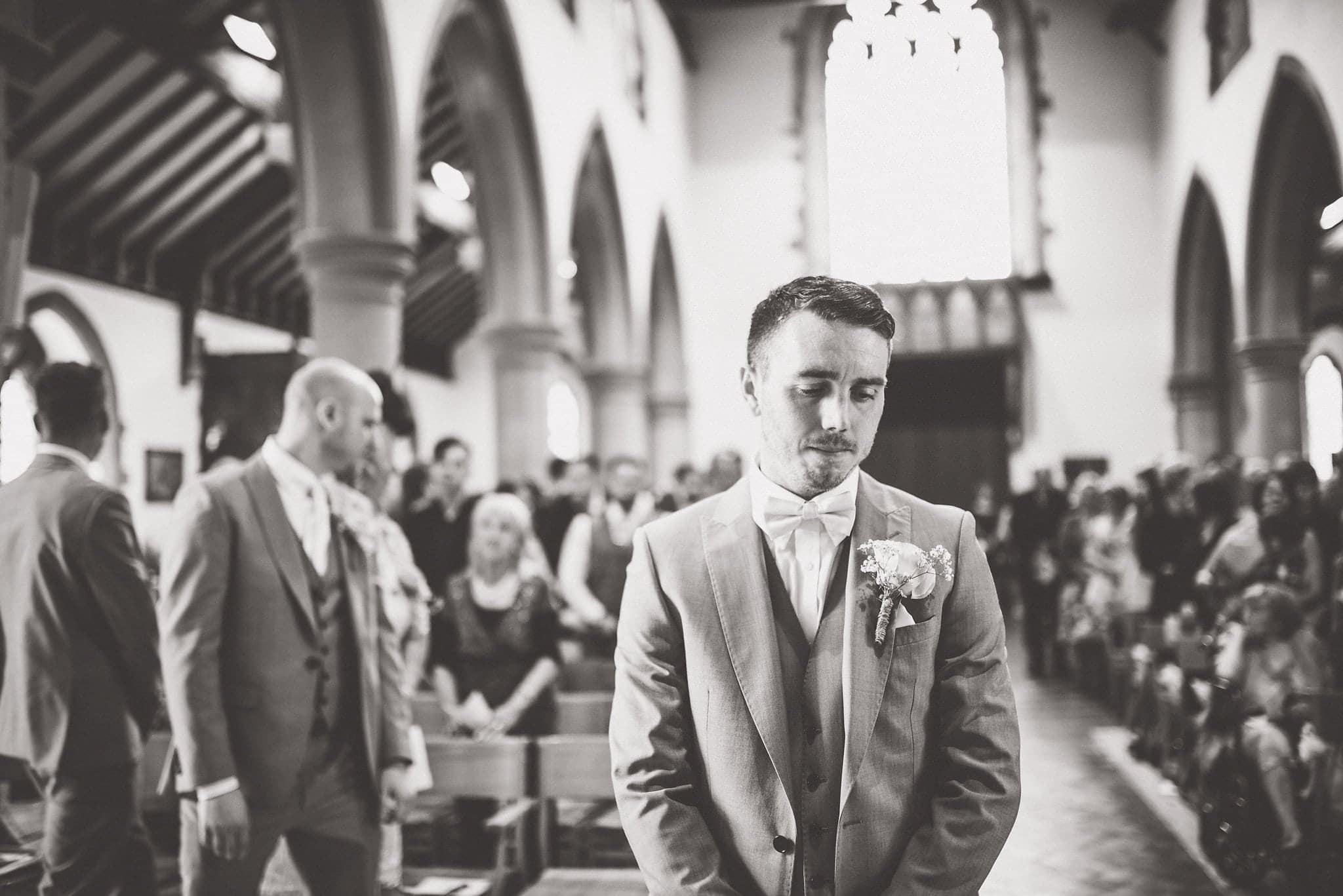 Black and white shot of groom waiting for bride to arrive in church