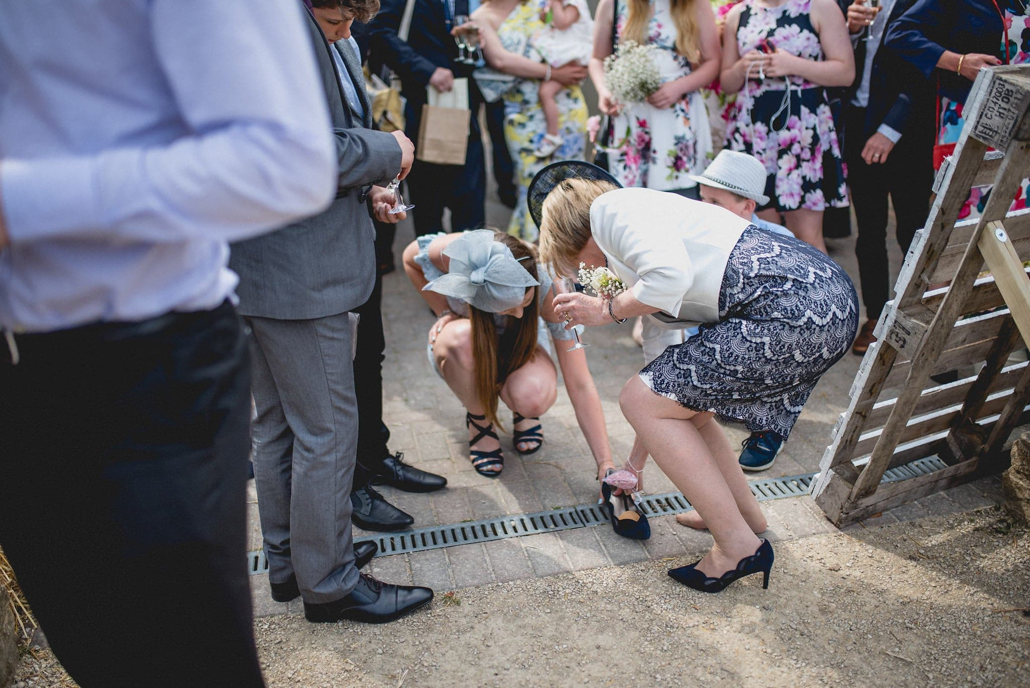 Guests help each other with their heels at this relaxed Fison Barn wedding