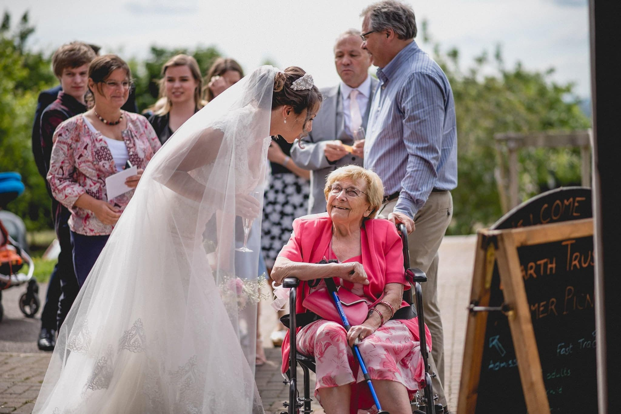 Bride speaks to older guest in wheelchair