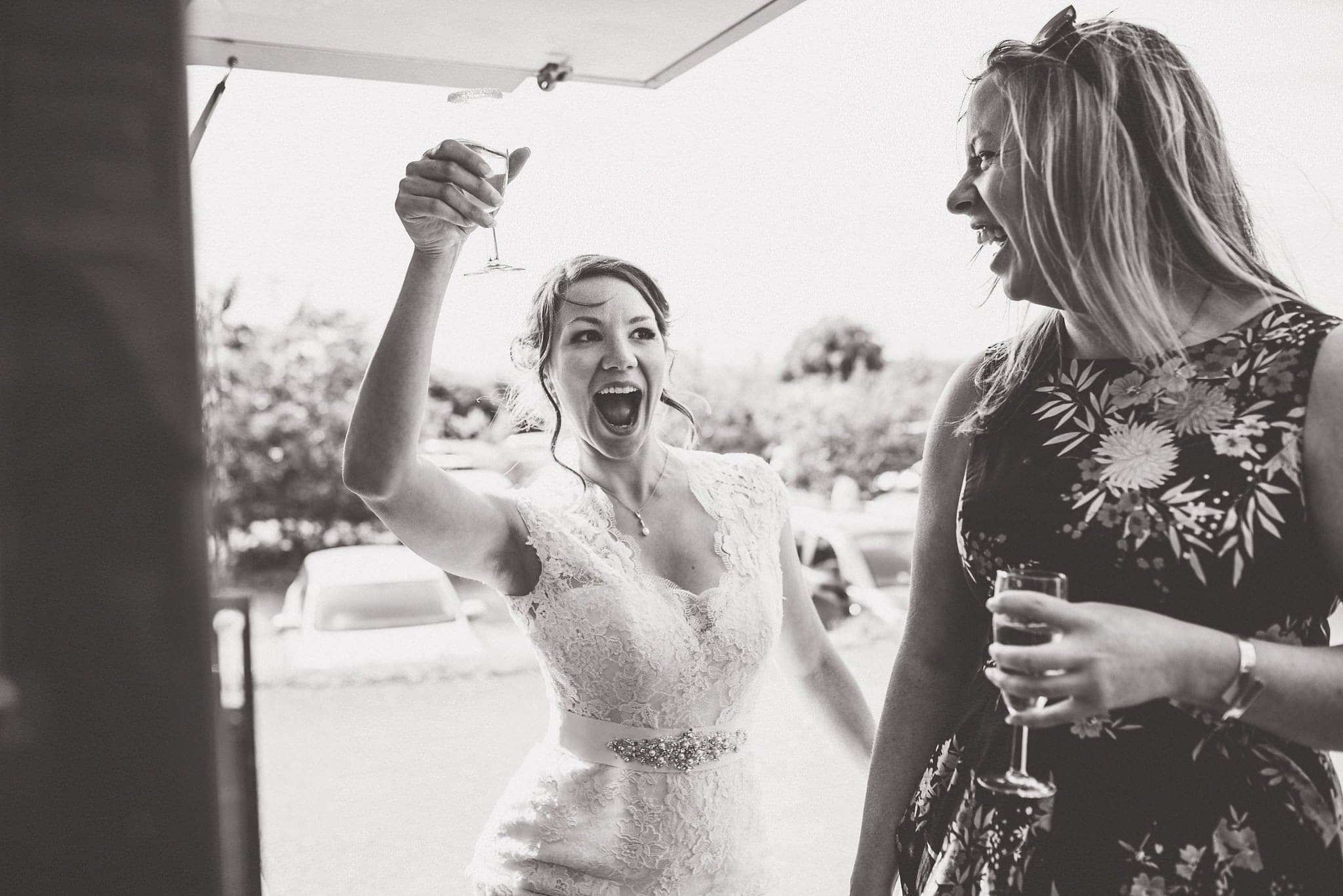 Bride raises enthusiastic toast with a friend