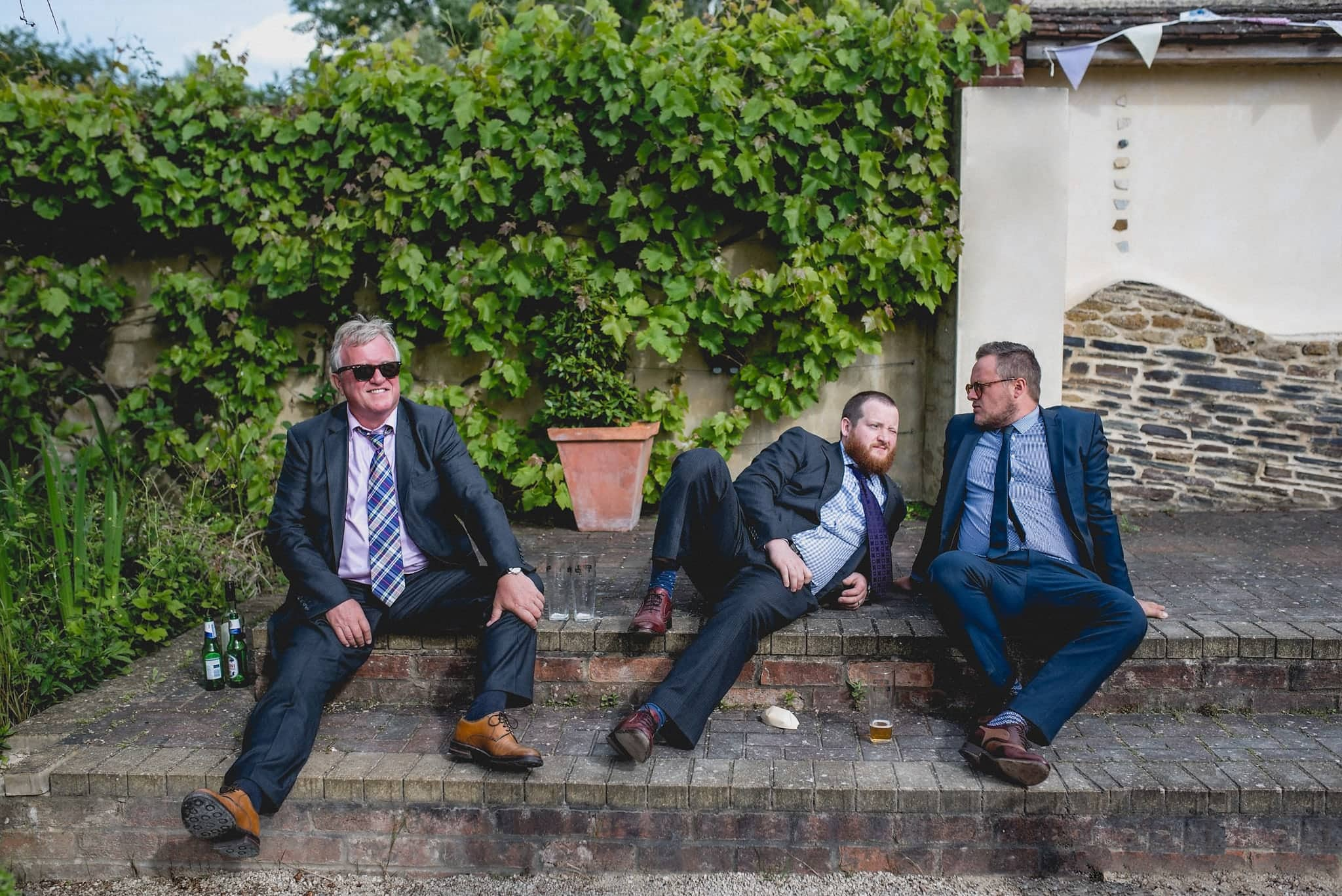 Male guests relax on steps in Fison Barn courtyard