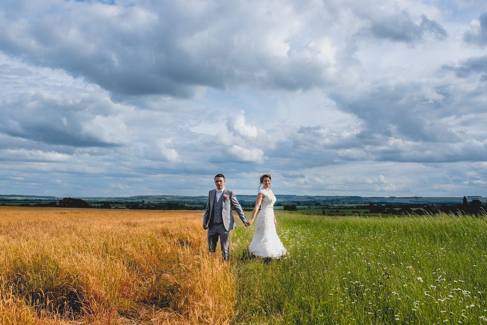 Bride and groom hold hands and stand on the border of two fields, one yellow, one green