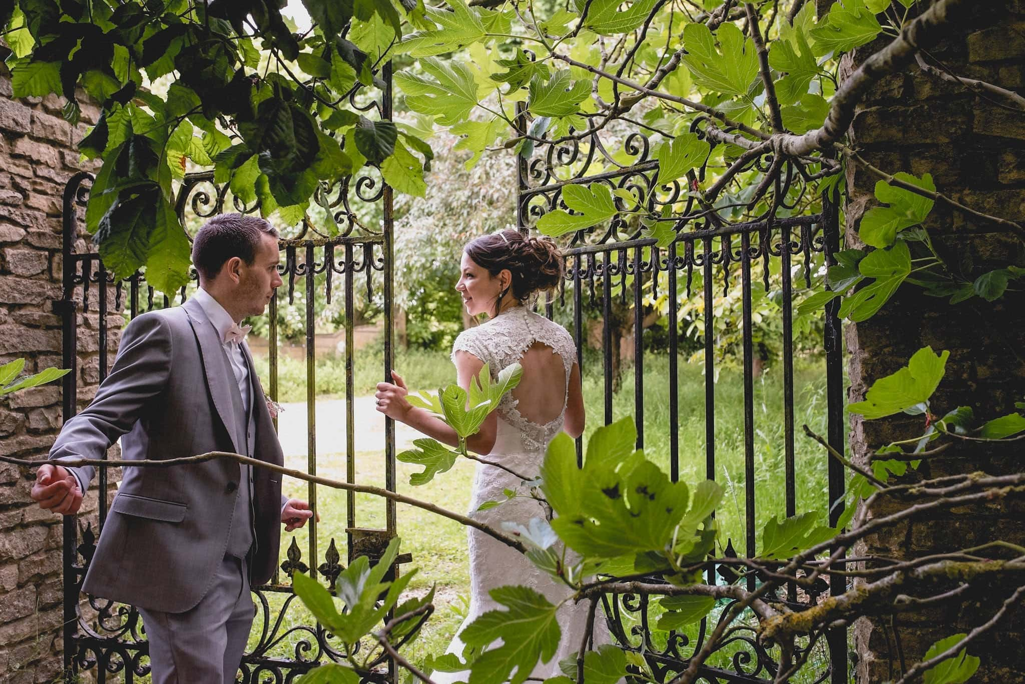 Bride and groom walk through wrought iron gate into fields for their couple's shoot