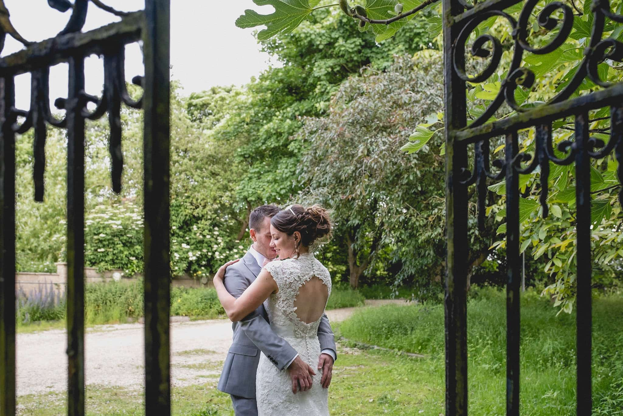 Bride and groom embrace in the grounds of Fison Barn, seen through a wrought iron gate