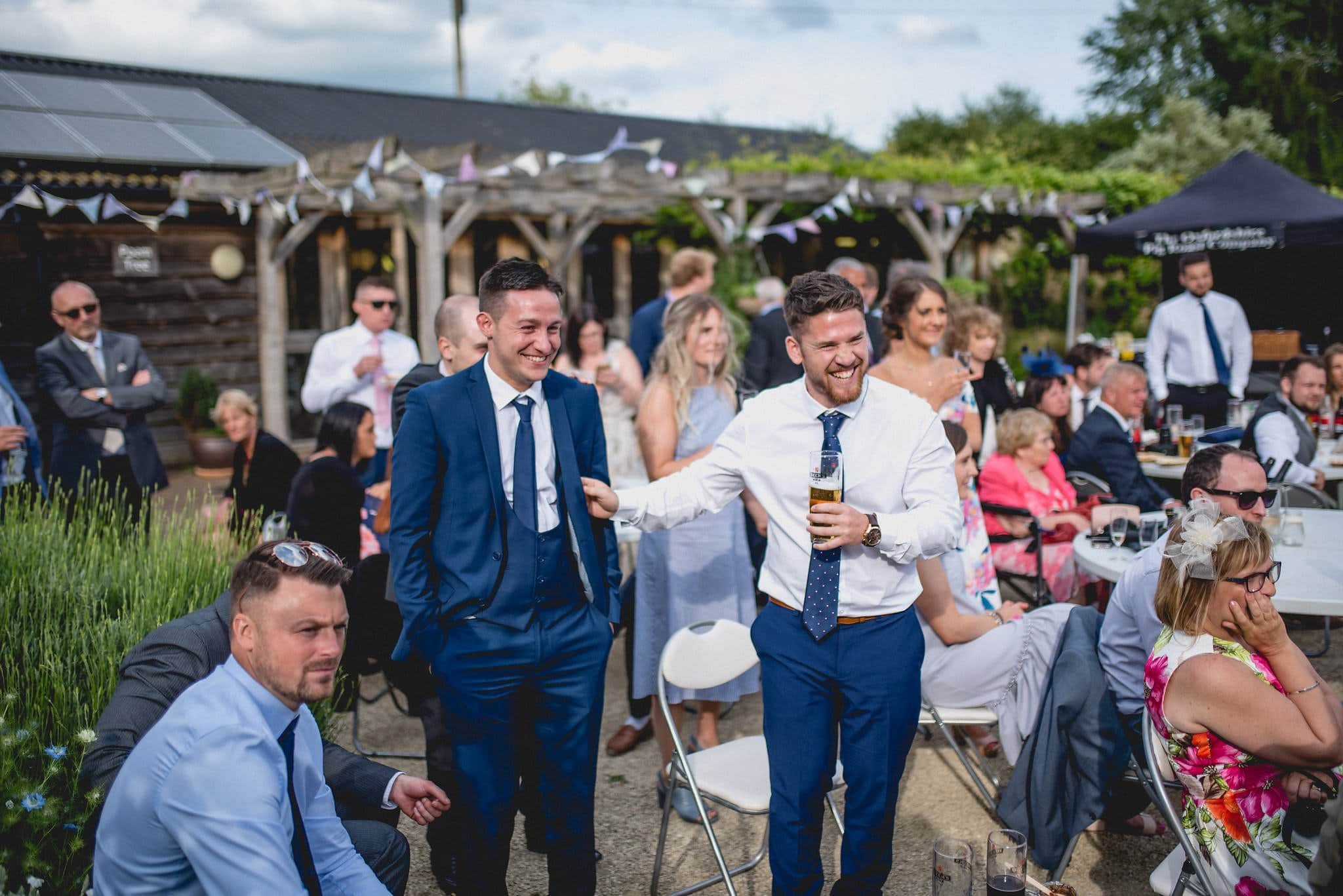 Guests laugh during wedding speeches in Fison Barn courtyard
