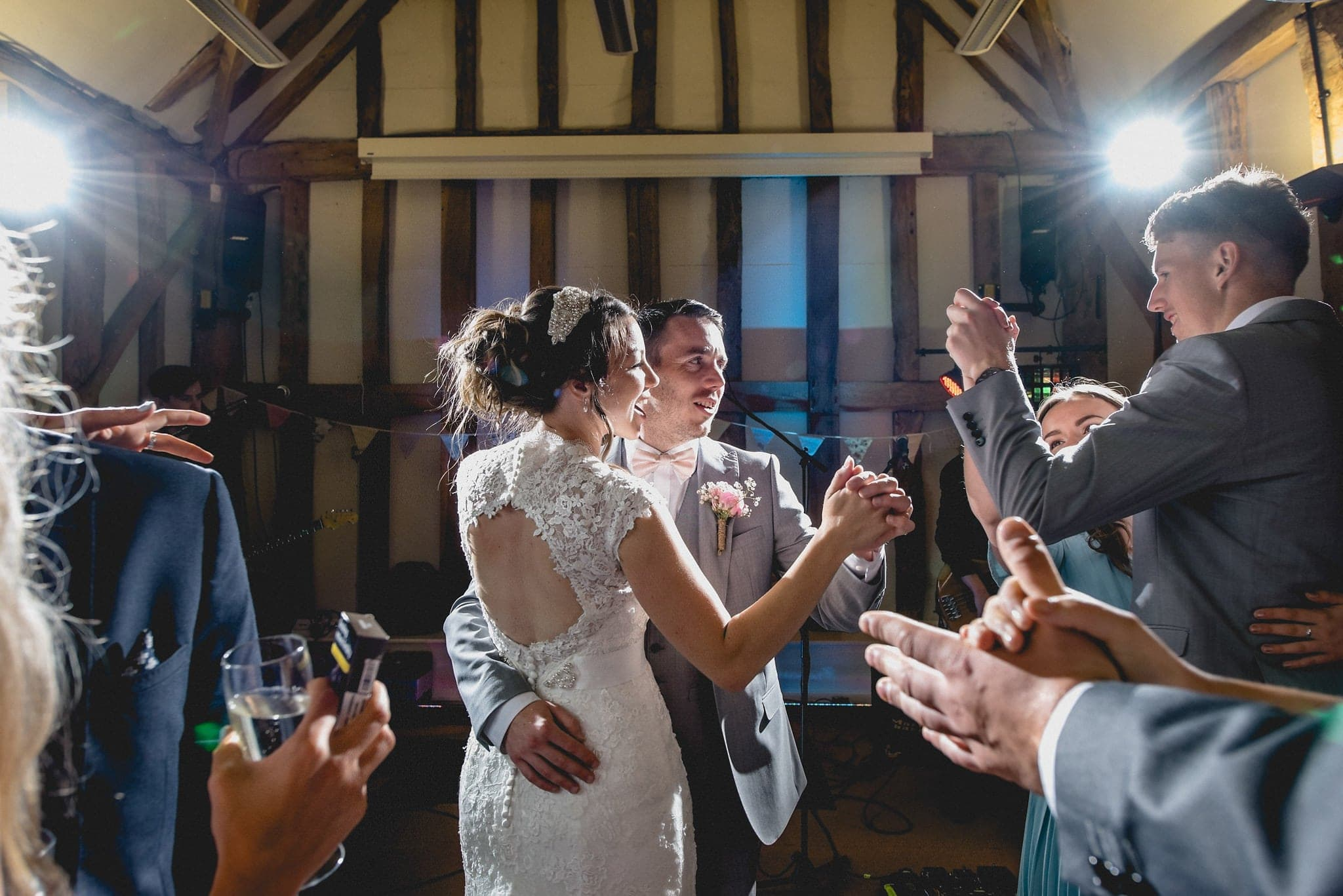 bride and groom laugh at their friends as they dance together