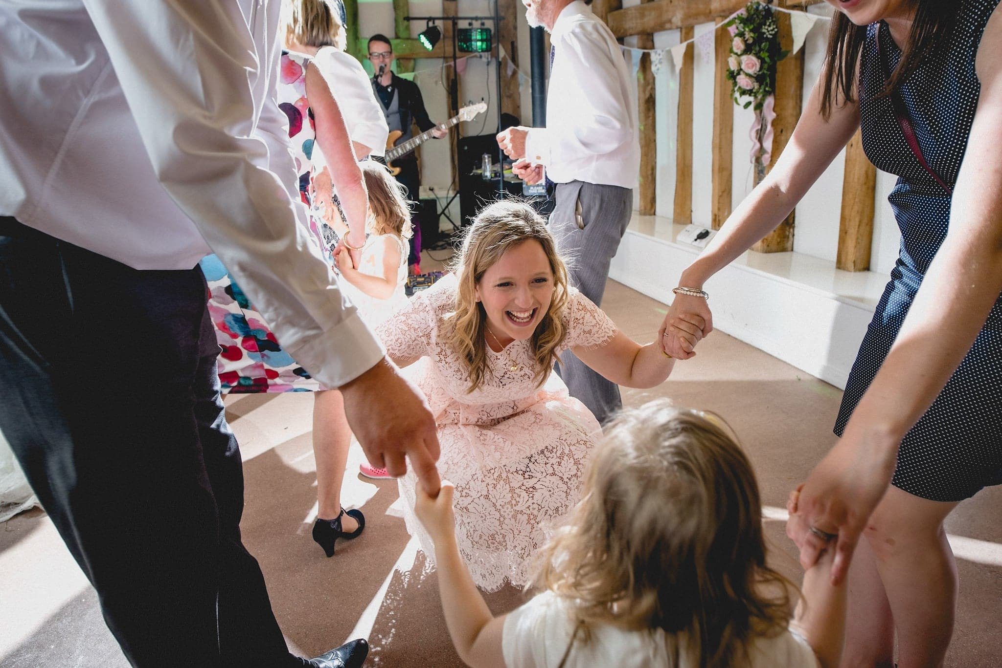 Bridesmaid kneels to dance with flower girl