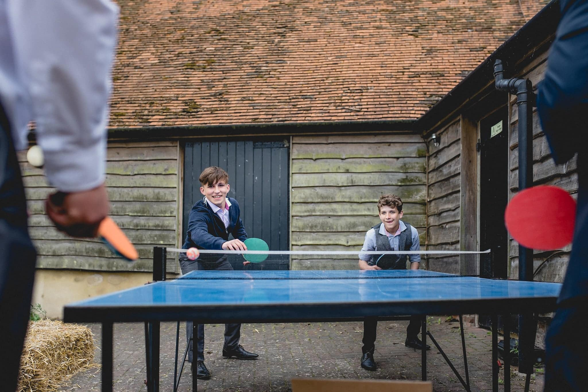 Kids play ping pong at relaxed Fison Barn wedding