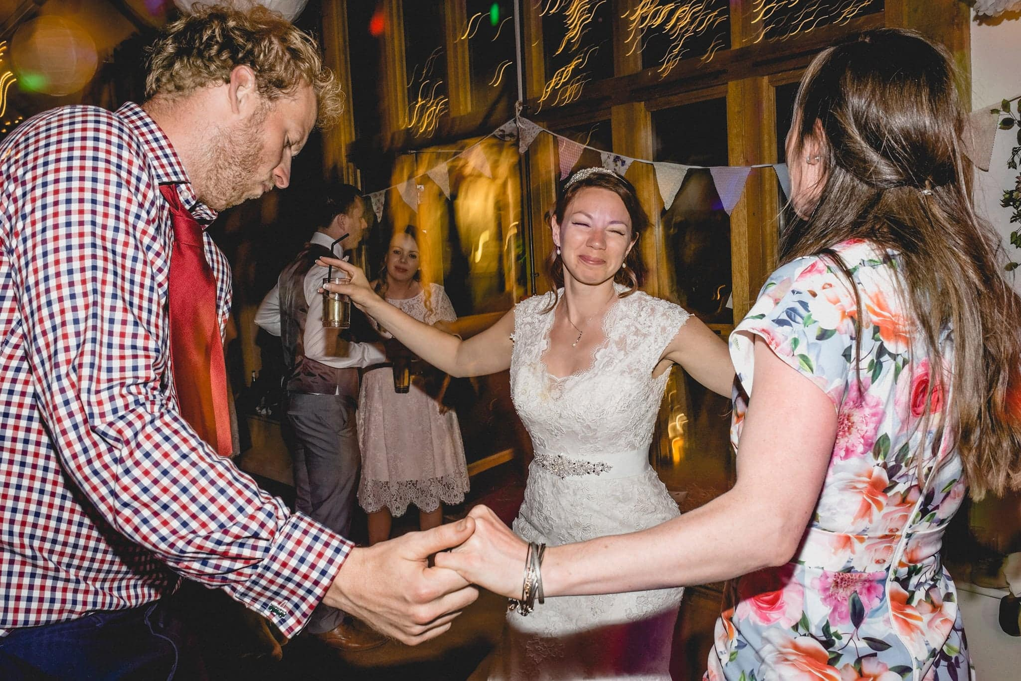 Bride dances with friends on dancefloor at her relaxed Fison Barn Wedding