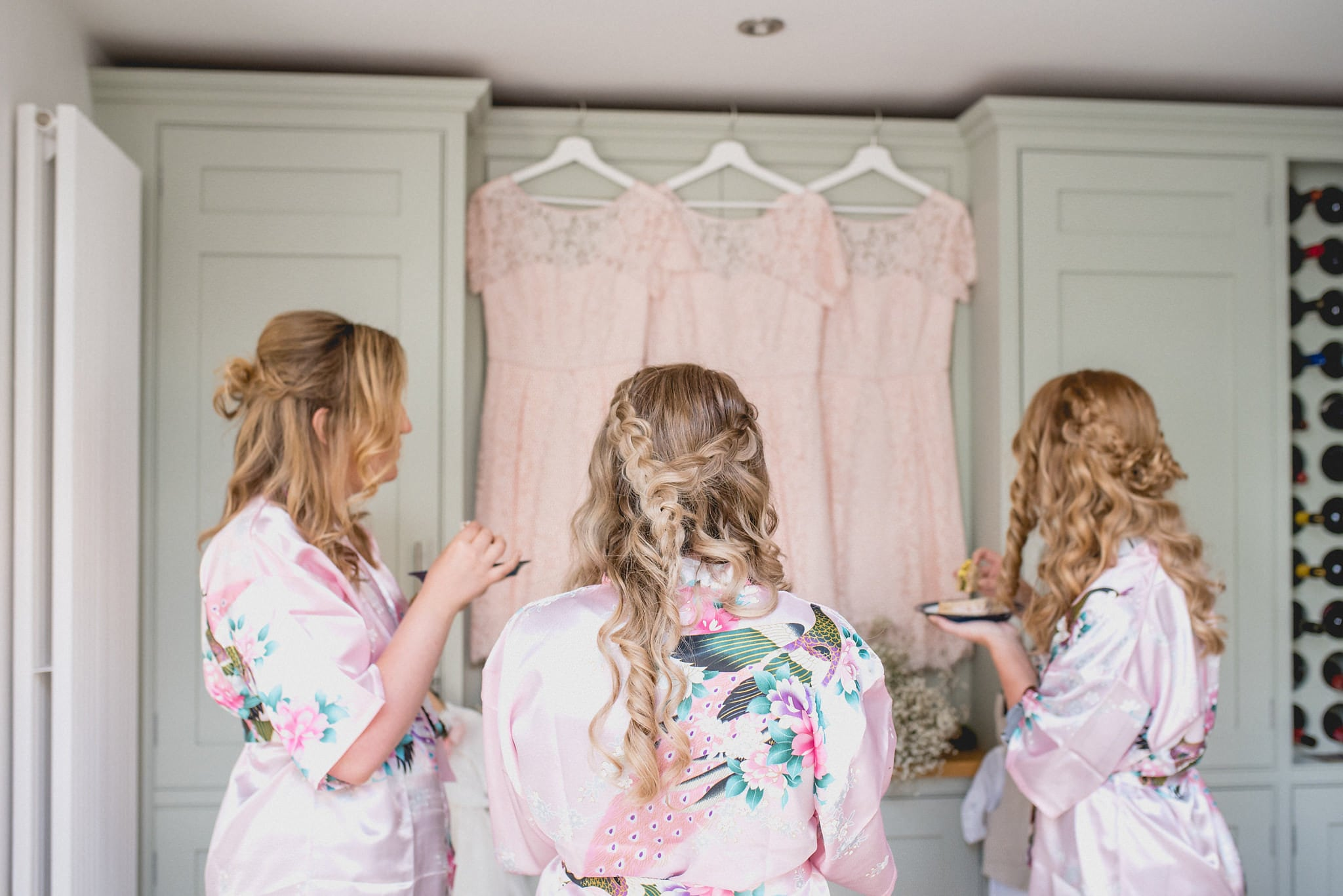 Bridesmaids in morning gowns look at their dresses hanging on a cupboard