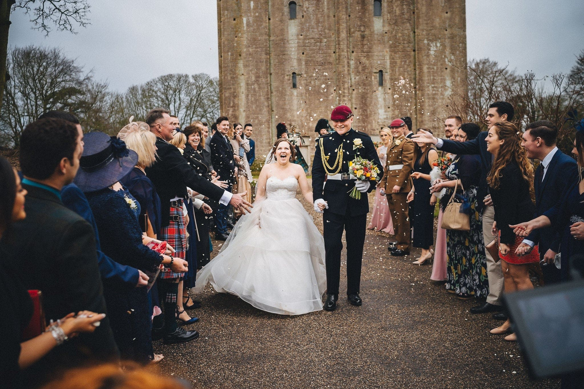 Bride and groom walk through confetti at Hedingham Castle