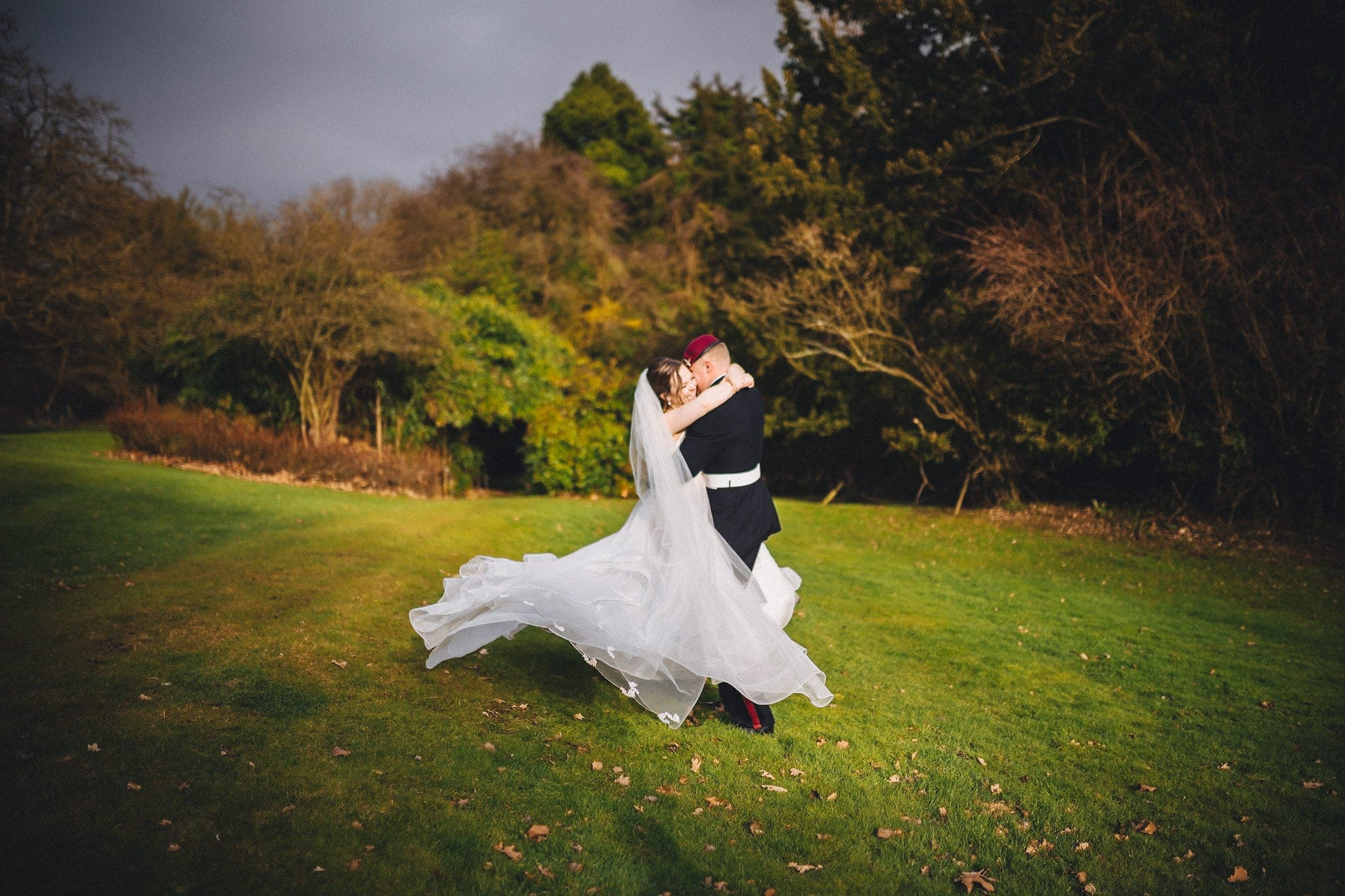 Groom lifts his bride off the floor in grounds of Hedingham Castle