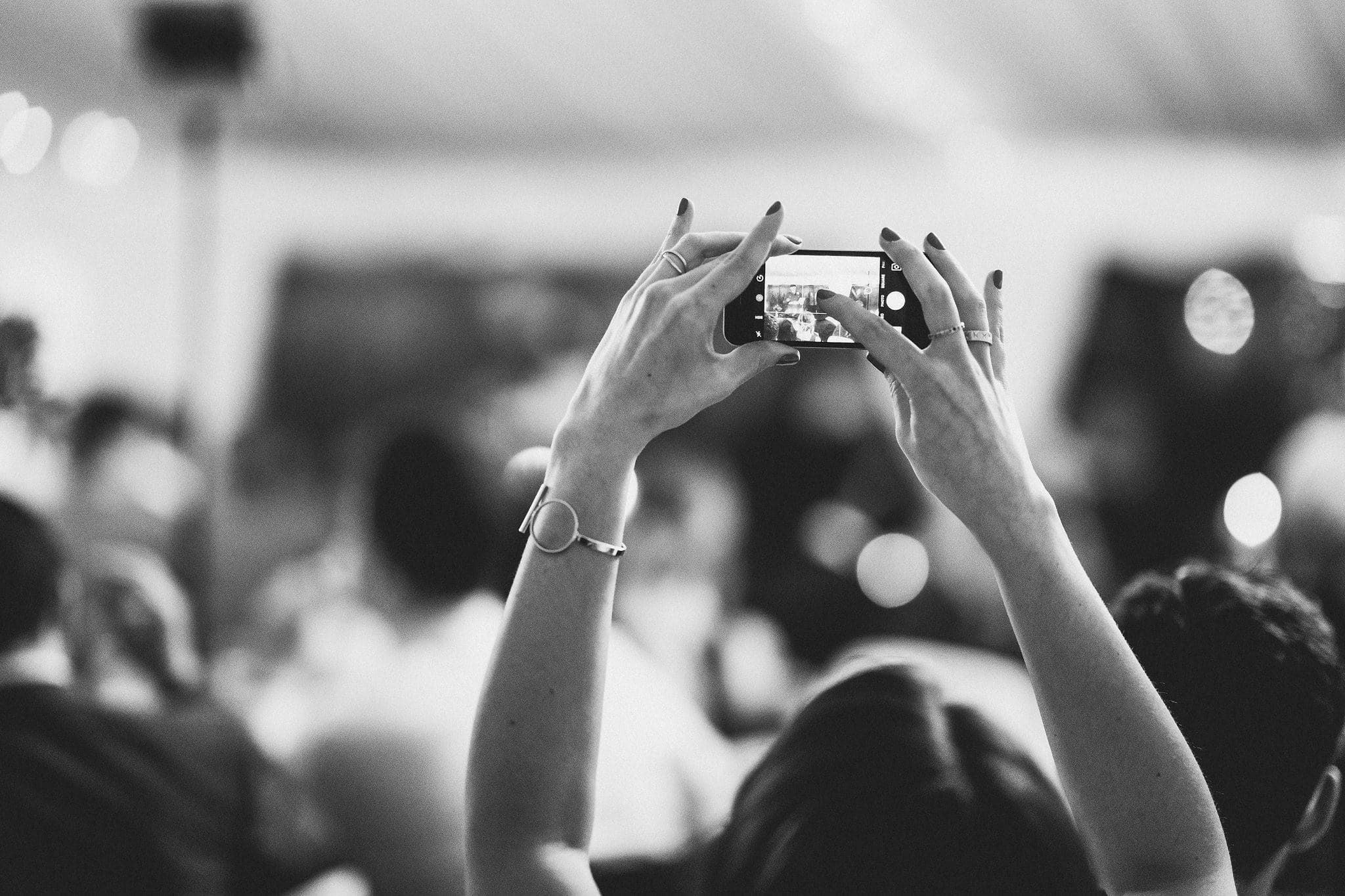 Black and white shot of guest taking a picture on their phone
