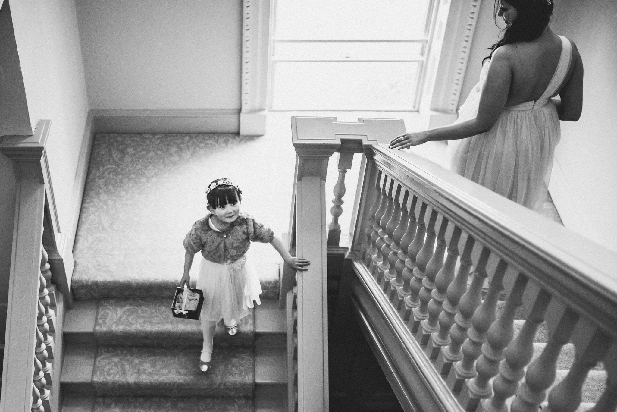 Flower girl walking down the main staircase at Morden Hall towards the wedding ceremony