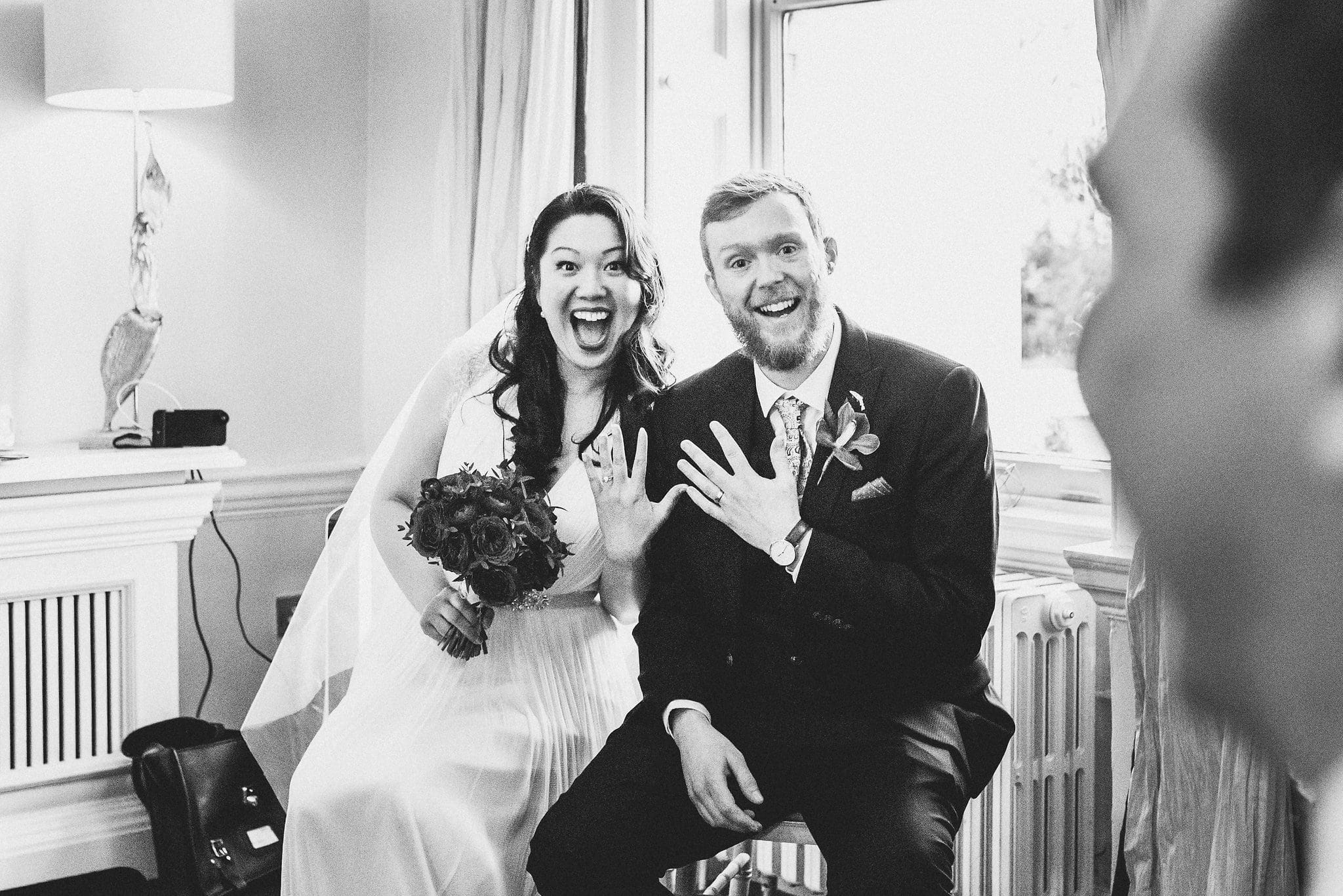 Newlywed bride and groom grin widely and show off their wedding rings
