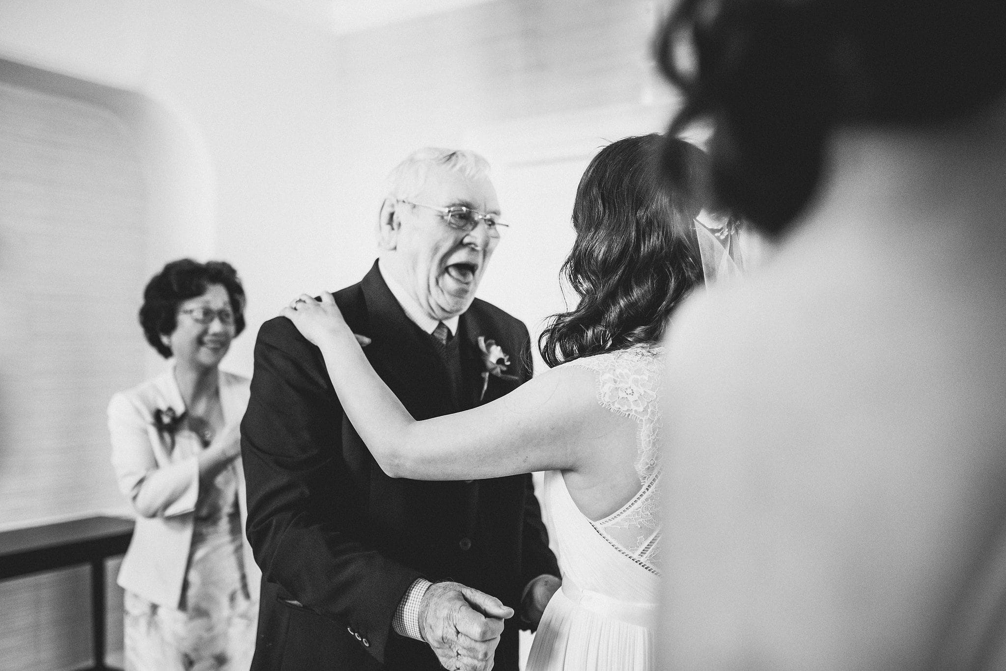 Bride shares a laugh with an her groom's grandad