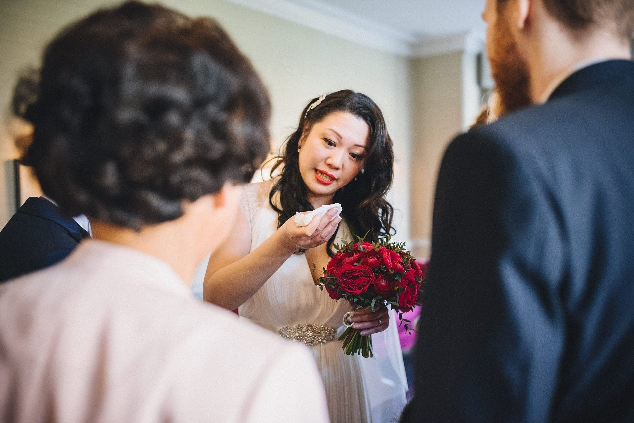 Bride gets emotional while holding red rose bouquet at her Fusion Morden Hall Wedding
