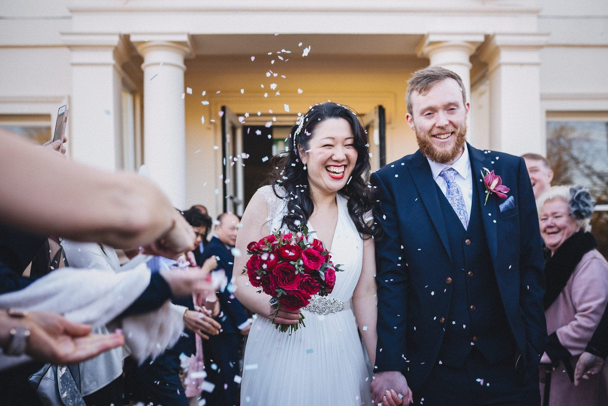 Bride and groom are showered in white confetti at Morden Hall