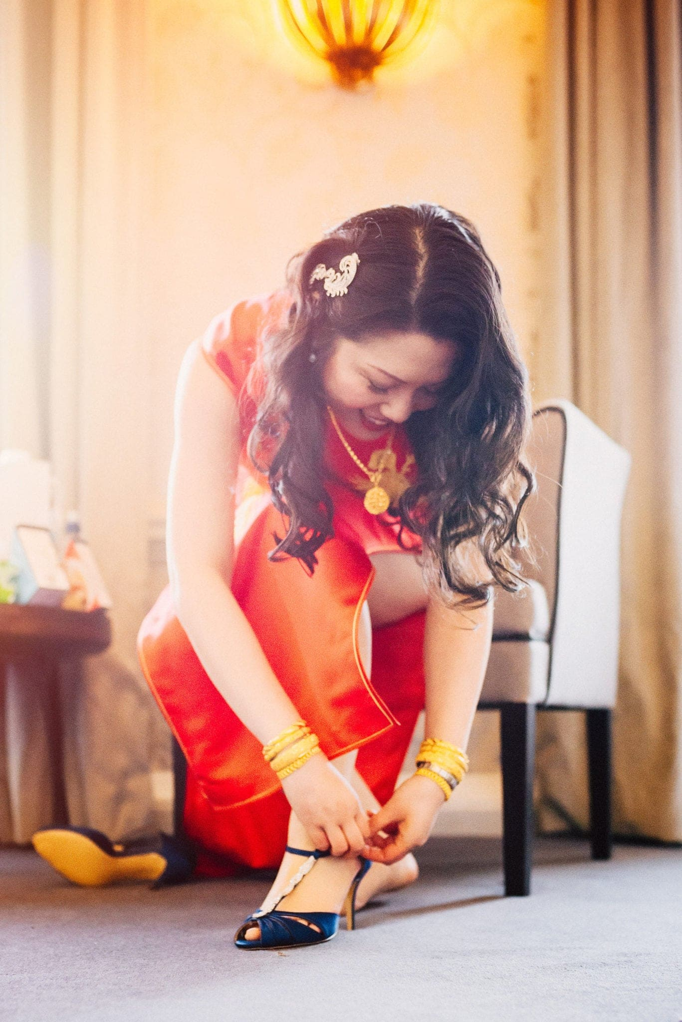 Bride fastens shoe, wearing scarlet silk dress flooded with light