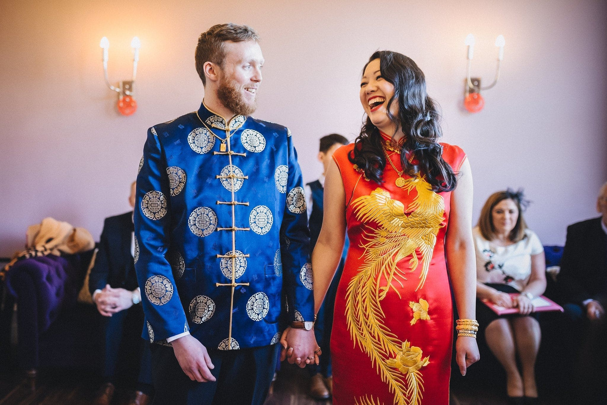 Bride and groom hold hands and laugh, wearing traditional Chinese silk dress and tunic