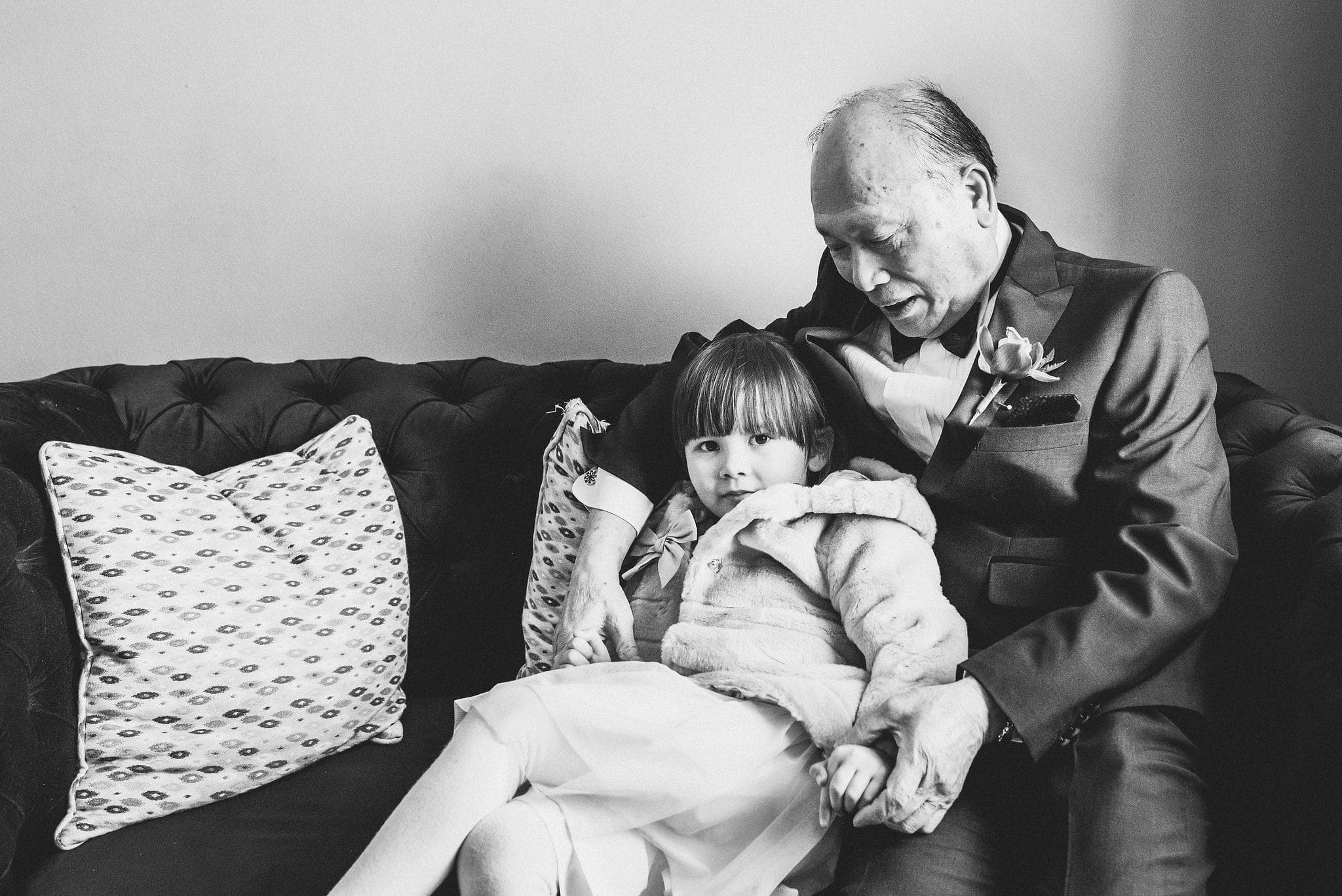 Black and white image of bride's father cuddling with flower girl on sofa