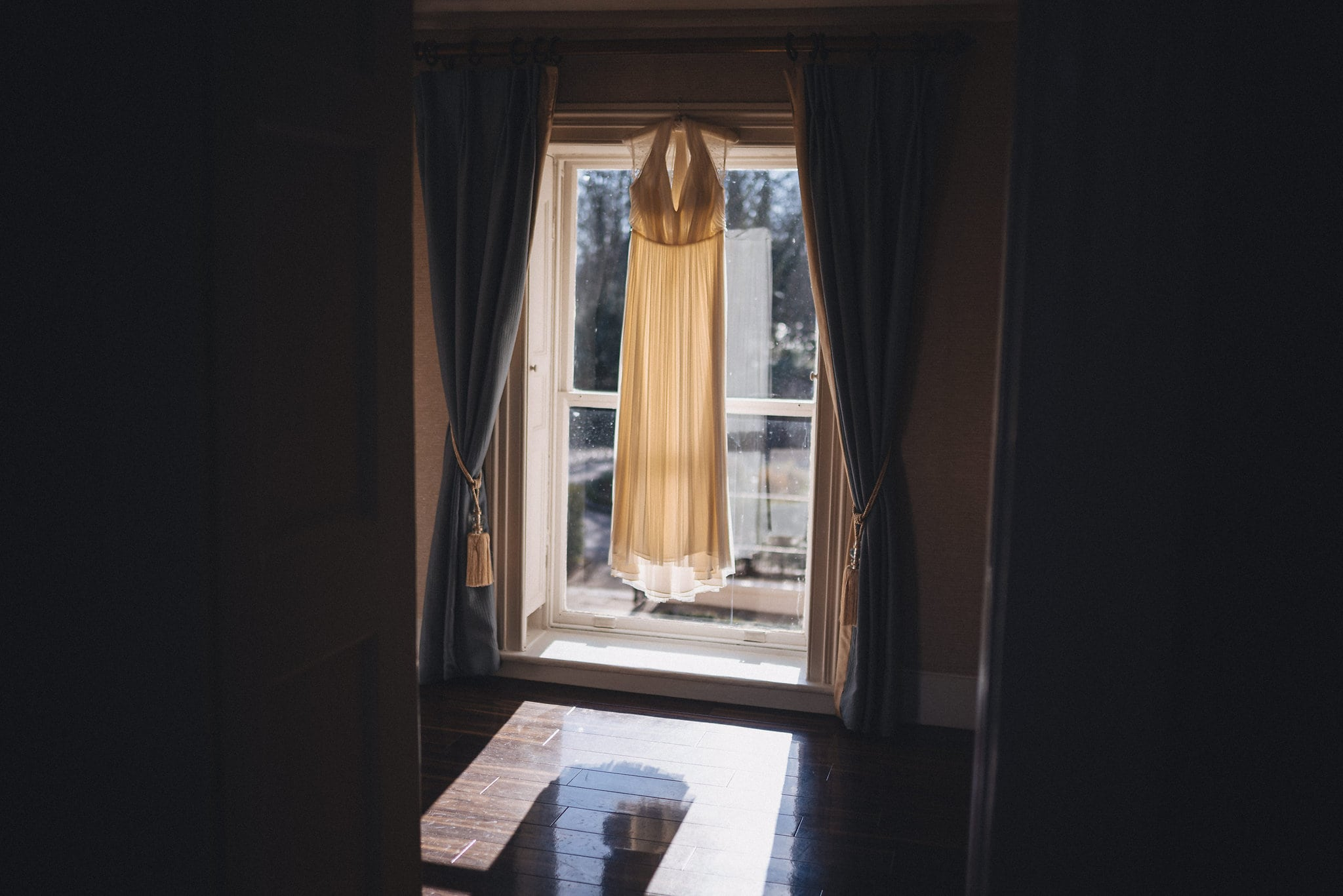 Wedding dress hanging in the window with sun streaming in at Morden Hall