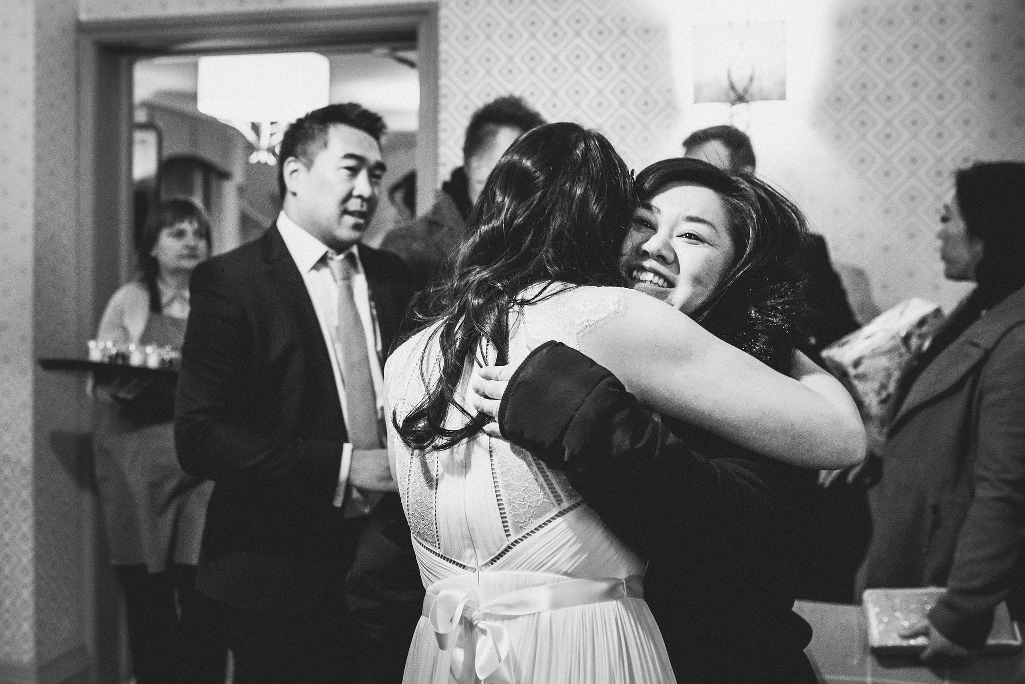 Bride hugs a wedding guest at Morden Hall