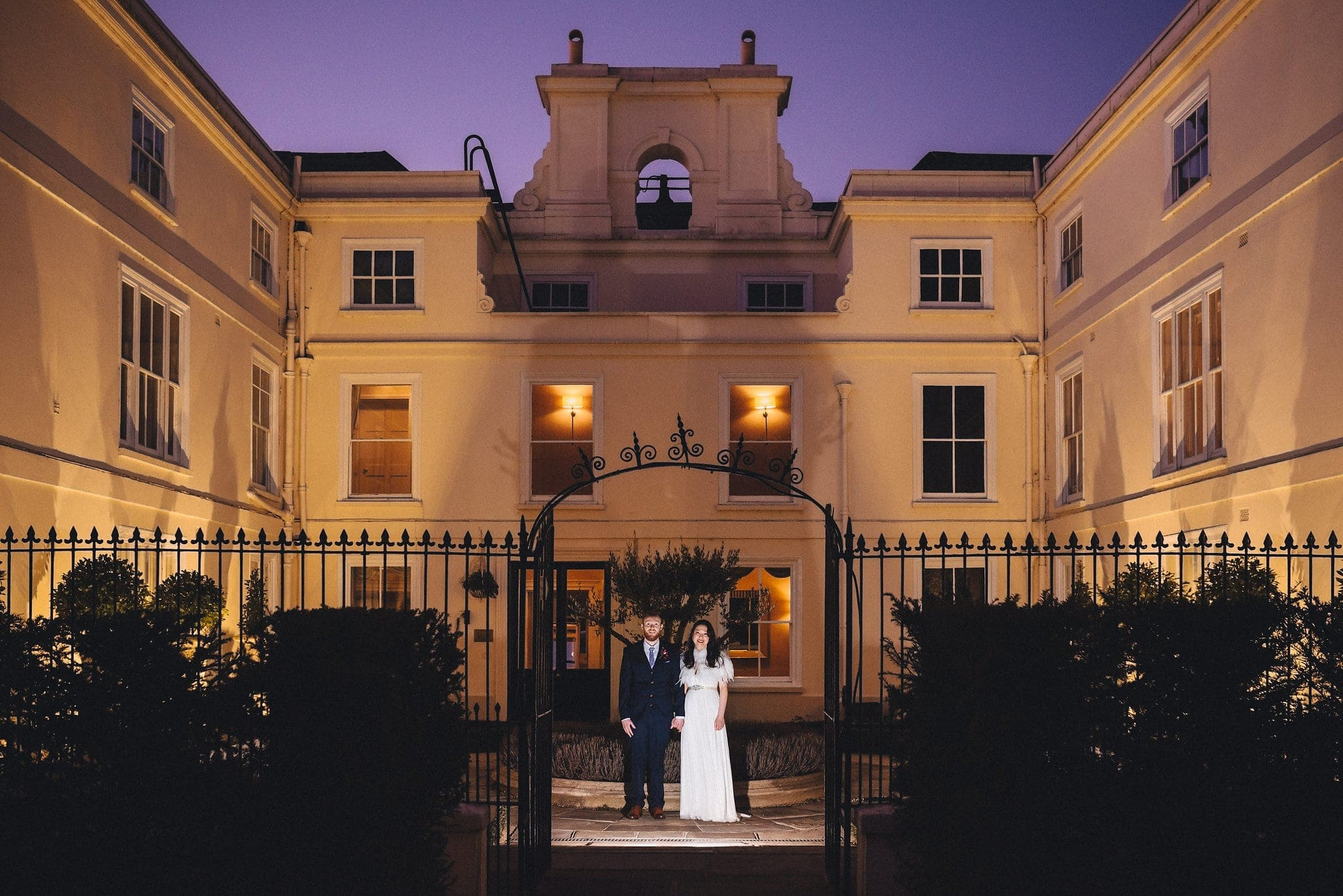 Bride and groom stand in front of Morden Hall for an evening shot at sunset