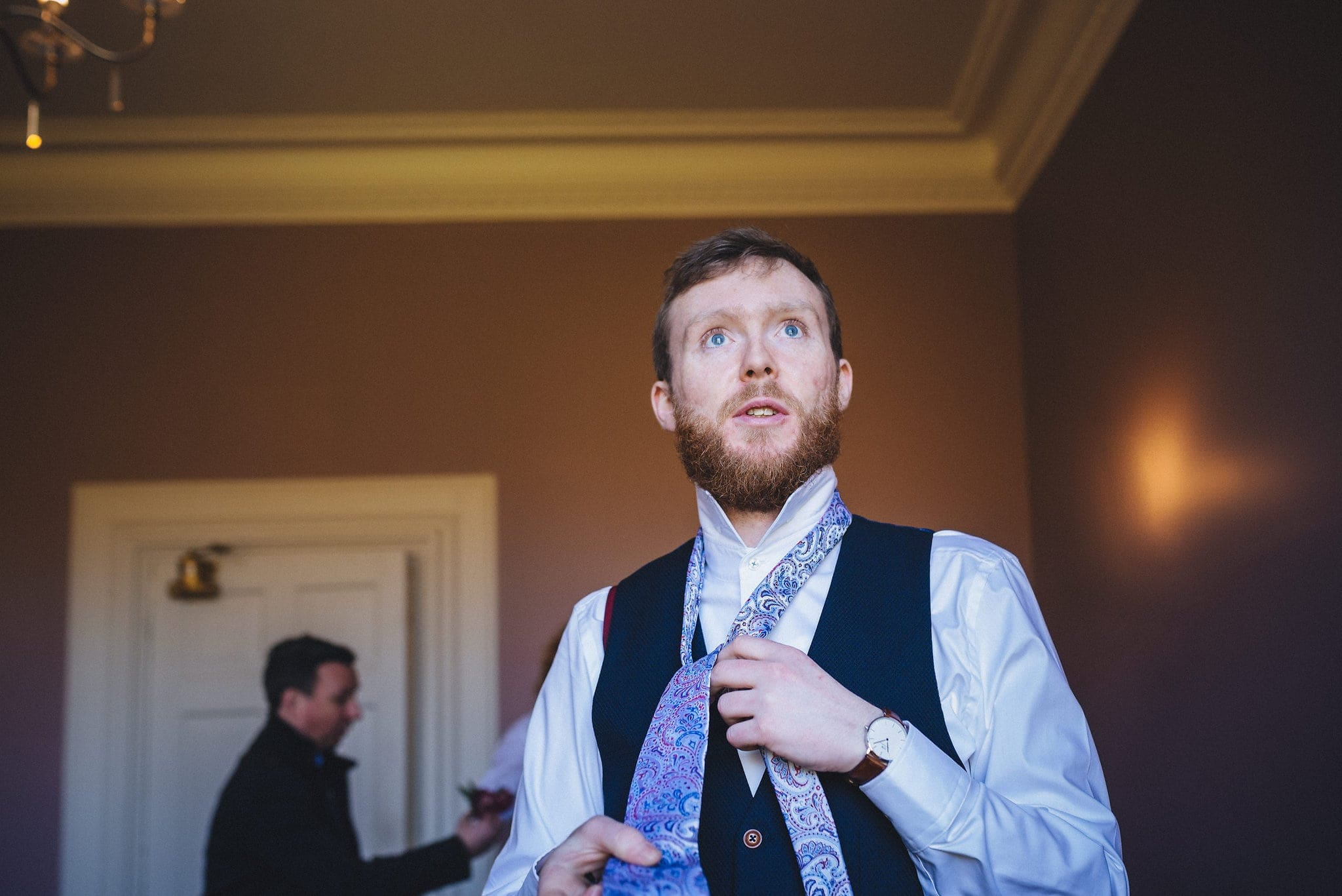 Groom ties paisley patterned tie