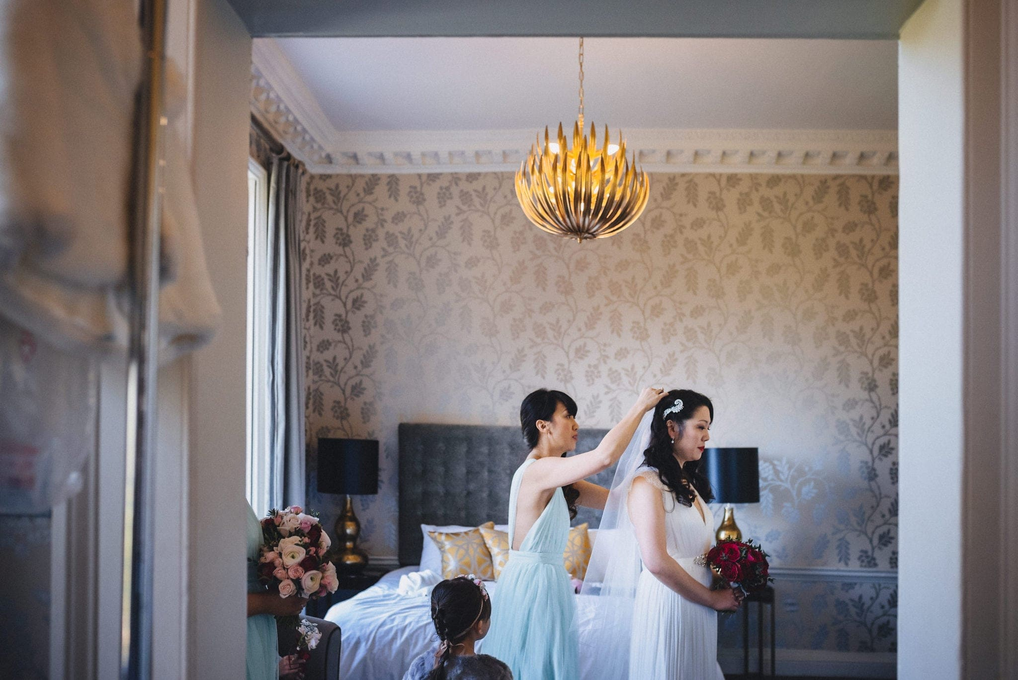 Bridesmaid putting in the bride's veil at her Fusion Morden Hall Wedding