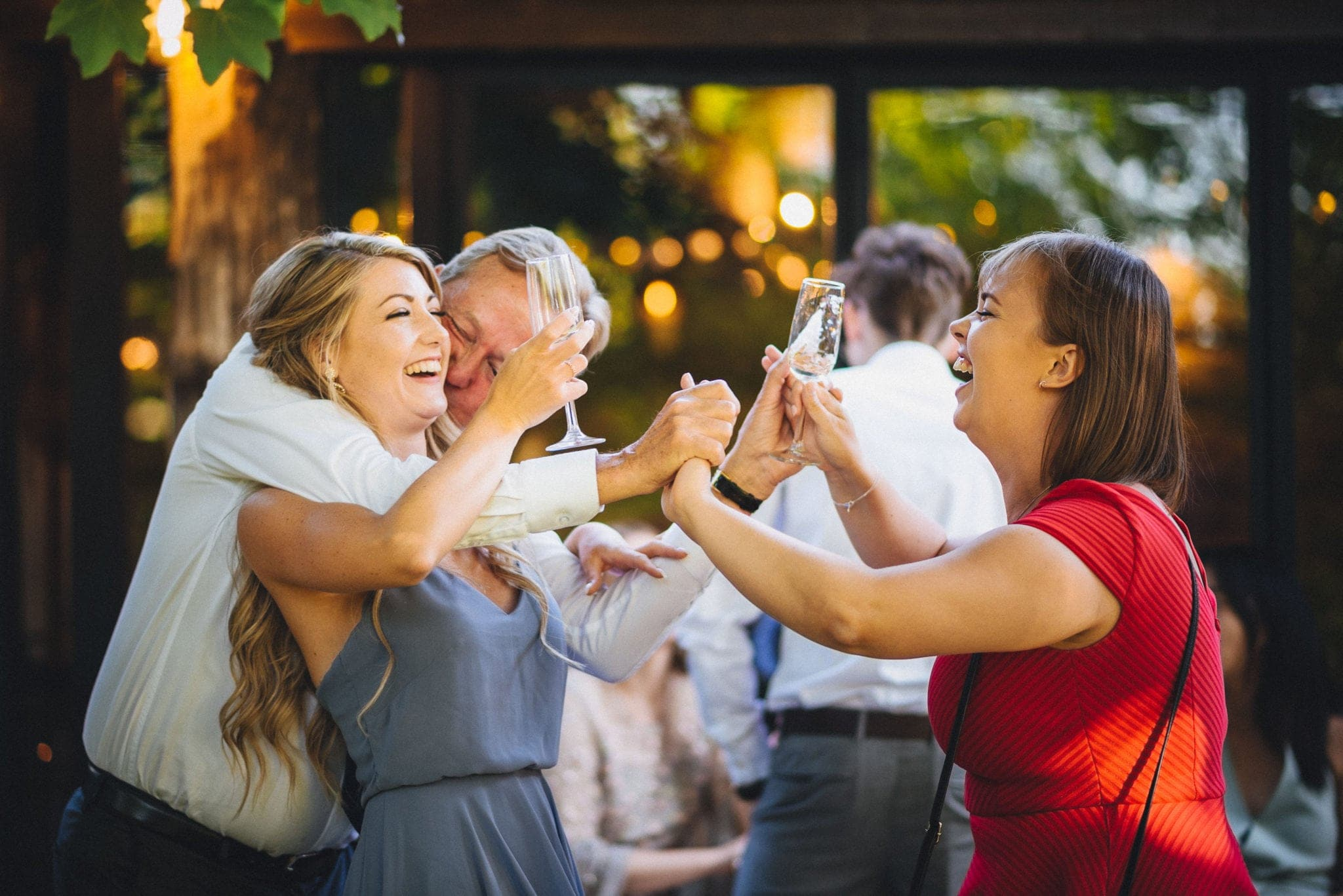 Wedding guests hugging and laughing while cheering with glasses