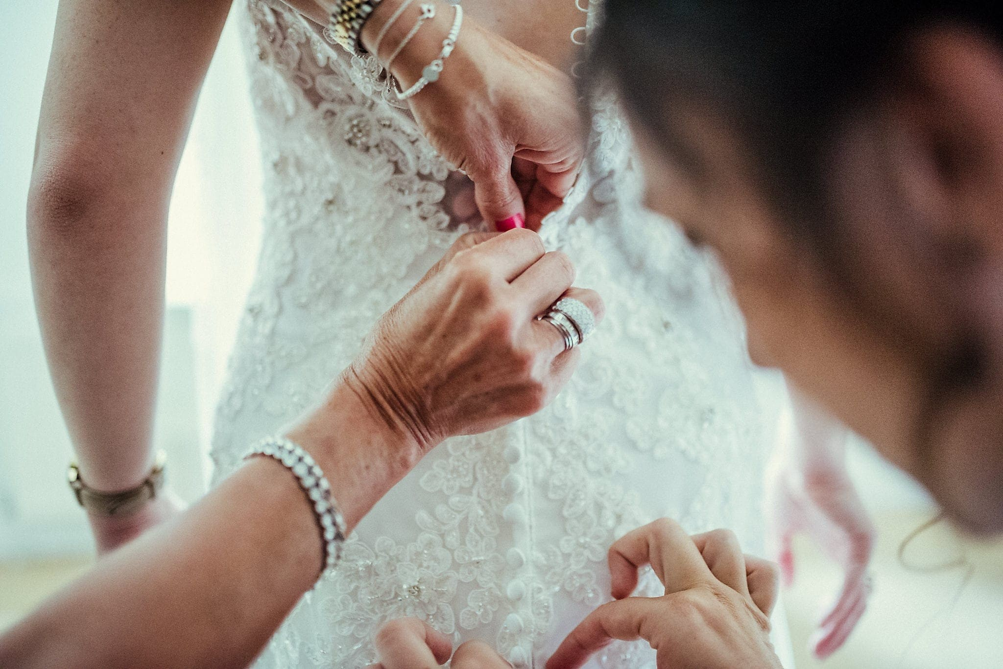 Hands fastening the bride's wedding dress buttons