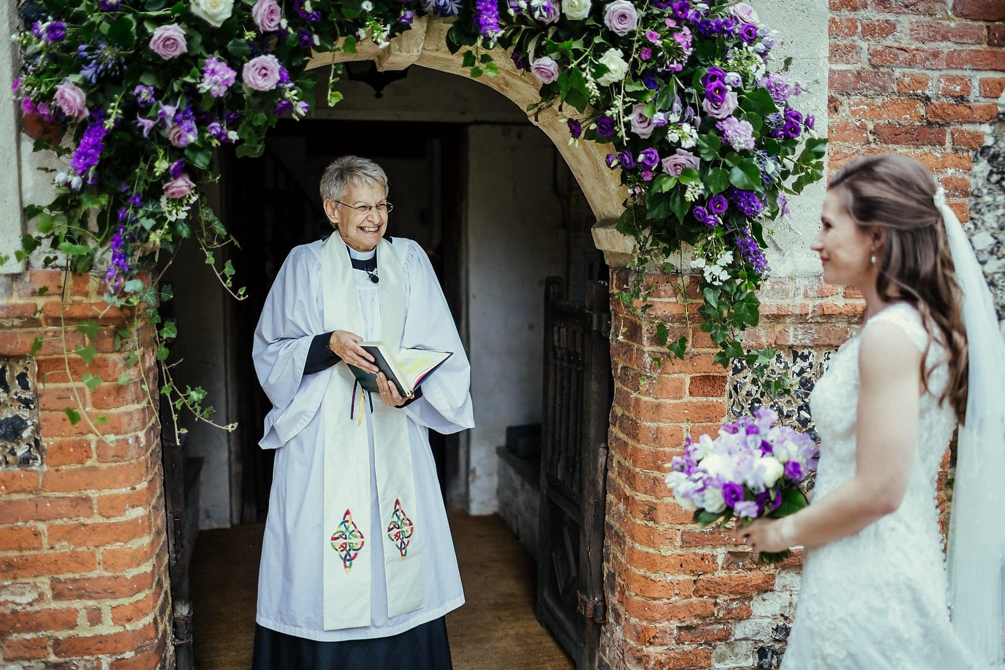 Documentary wedding photo of the vicar happily greeting the smiling bride