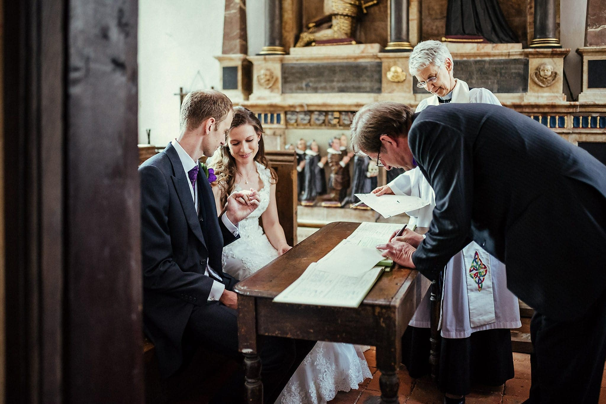 Bride and Groom look at each other's rings as their vicar signs their marriage certificate