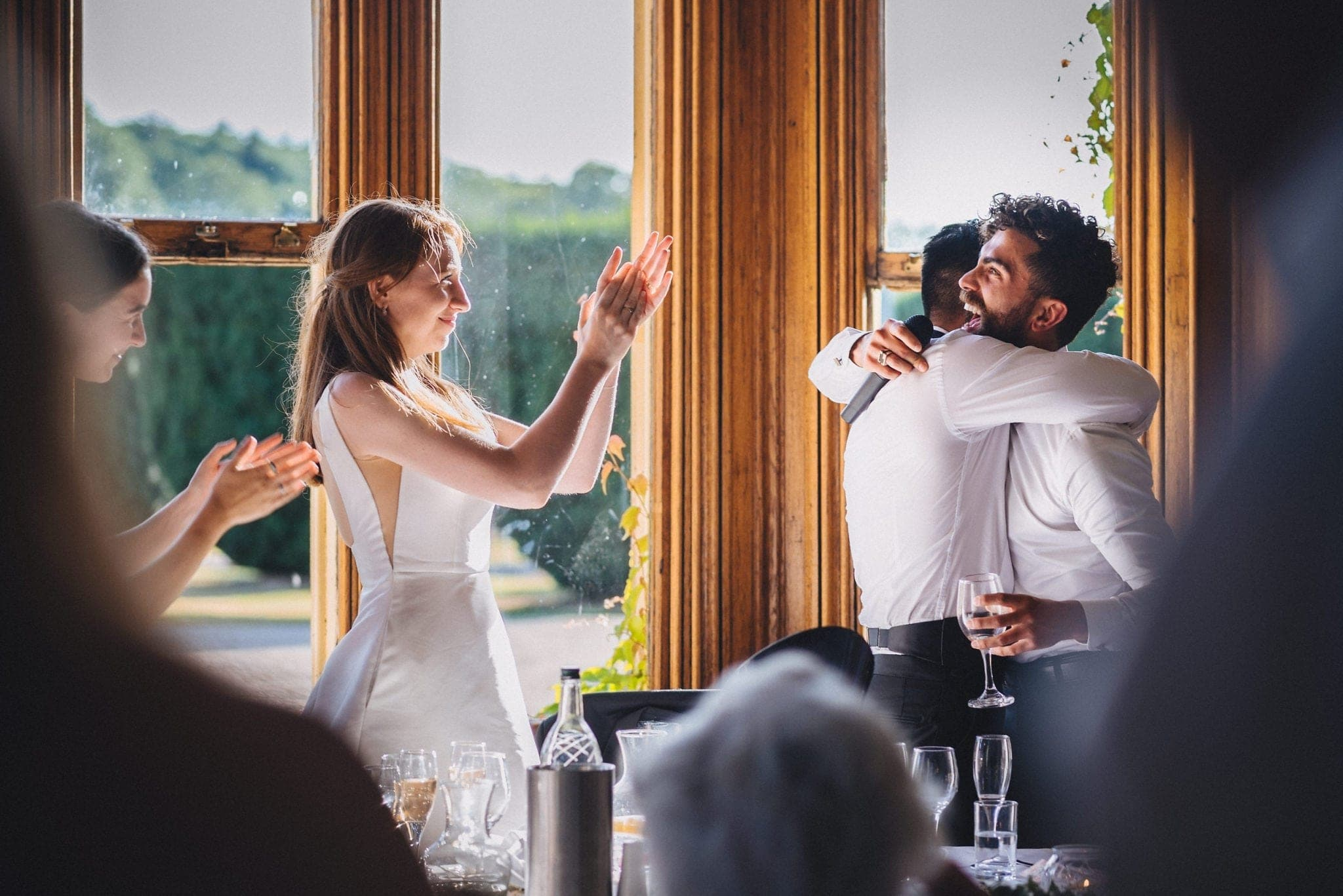 Bride clapping while groom hugs his laughing best man after his speech