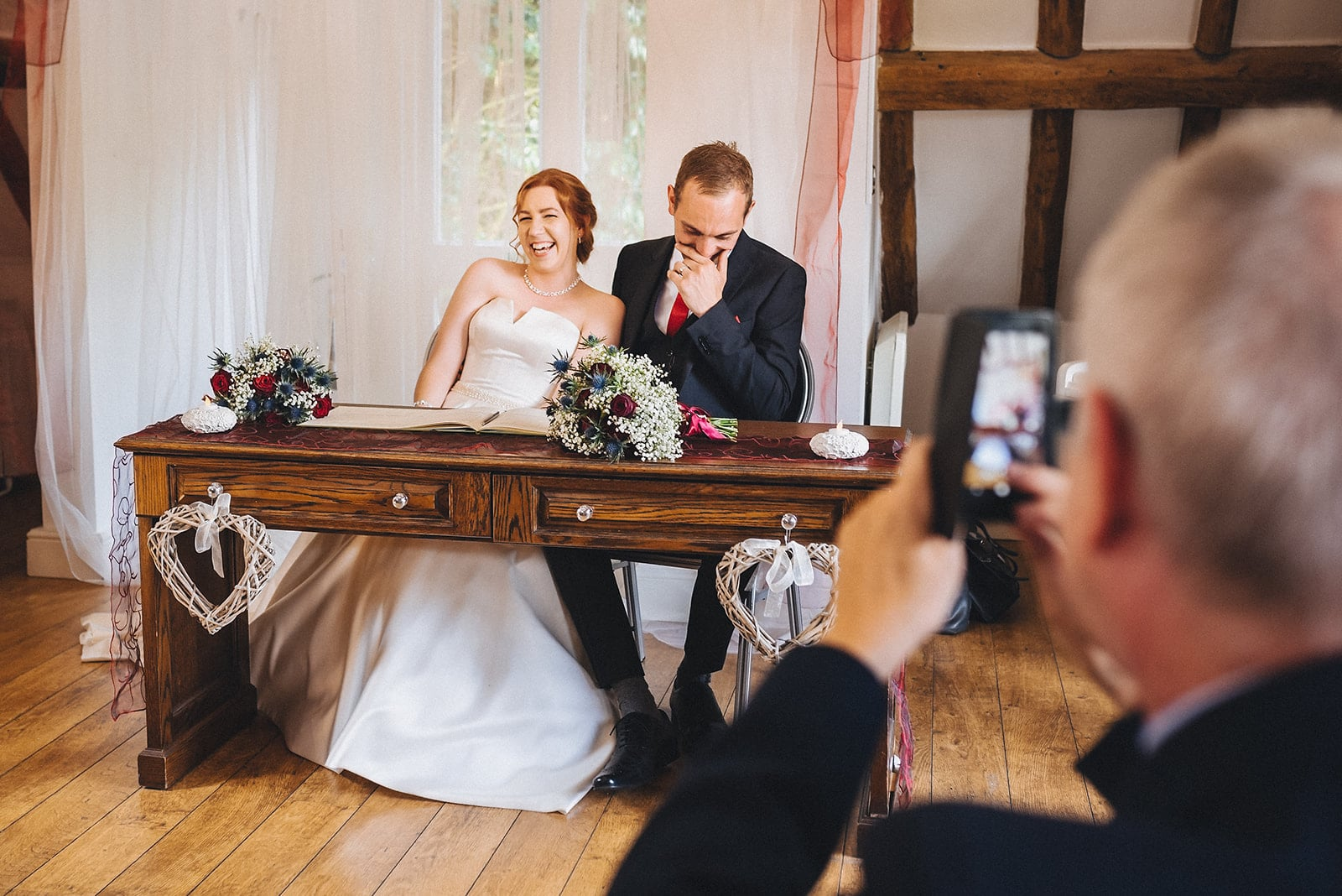 Bride and Groom laugh loud as they sign the marriage register at their Hever Hotel Wedding