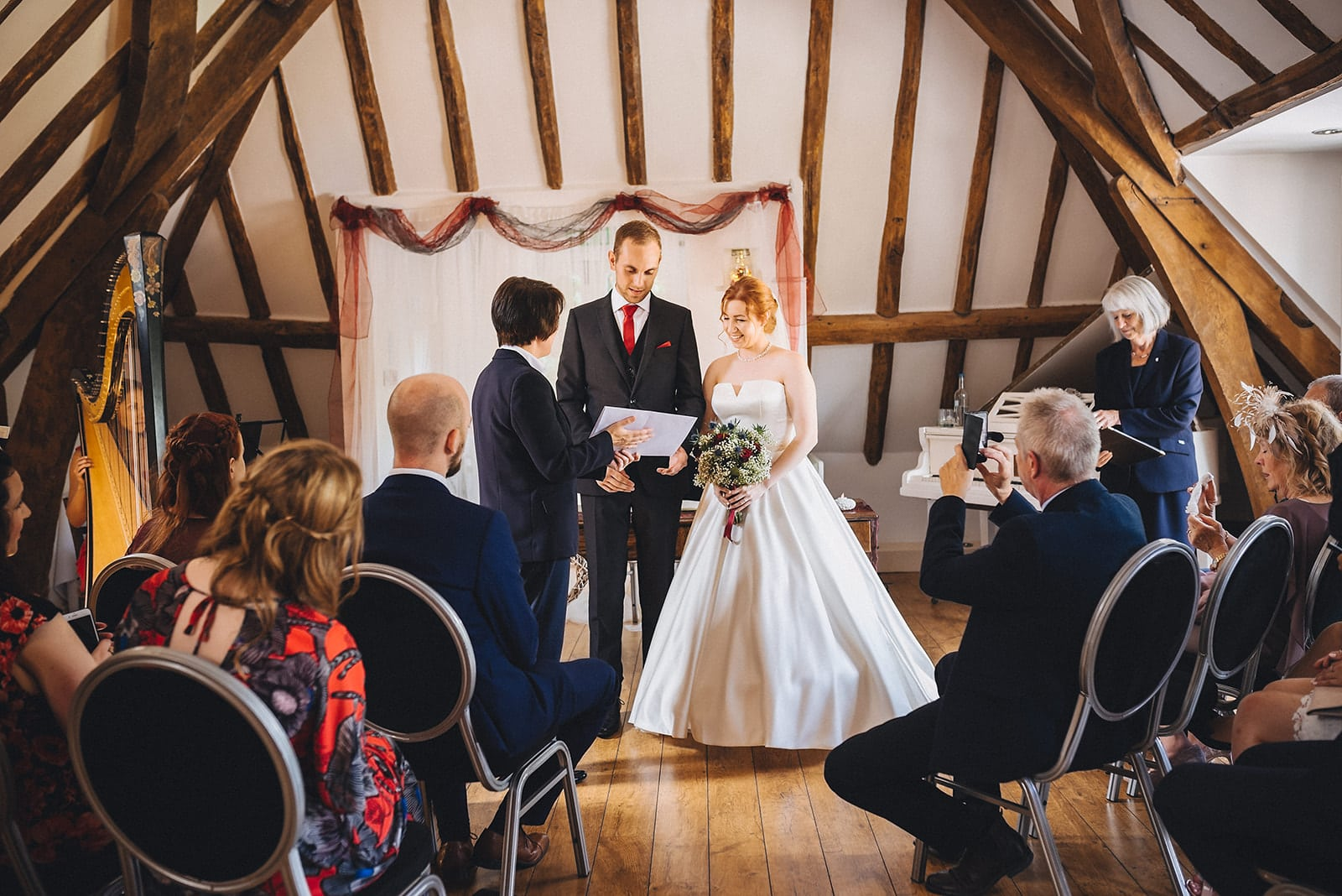 Registrar hands the bride and groom their marriage certificate at The Hever Hotel