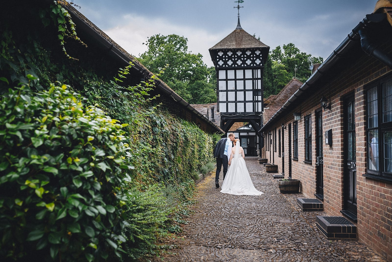 Bride and groom kiss as they walk down towards the main building of the Hever Hotel in Kent