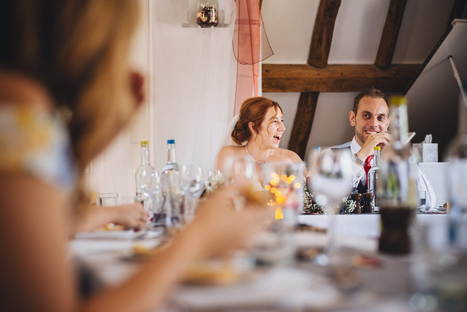 Bride and groom laugh at the speeches at their Hever Hotel Micro Wedding
