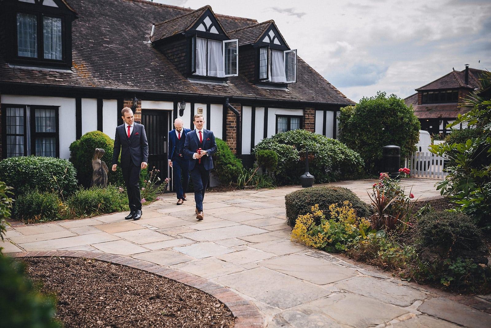 Groom and groomsmen walk towards a Hever Hotel Microwedding ceremony